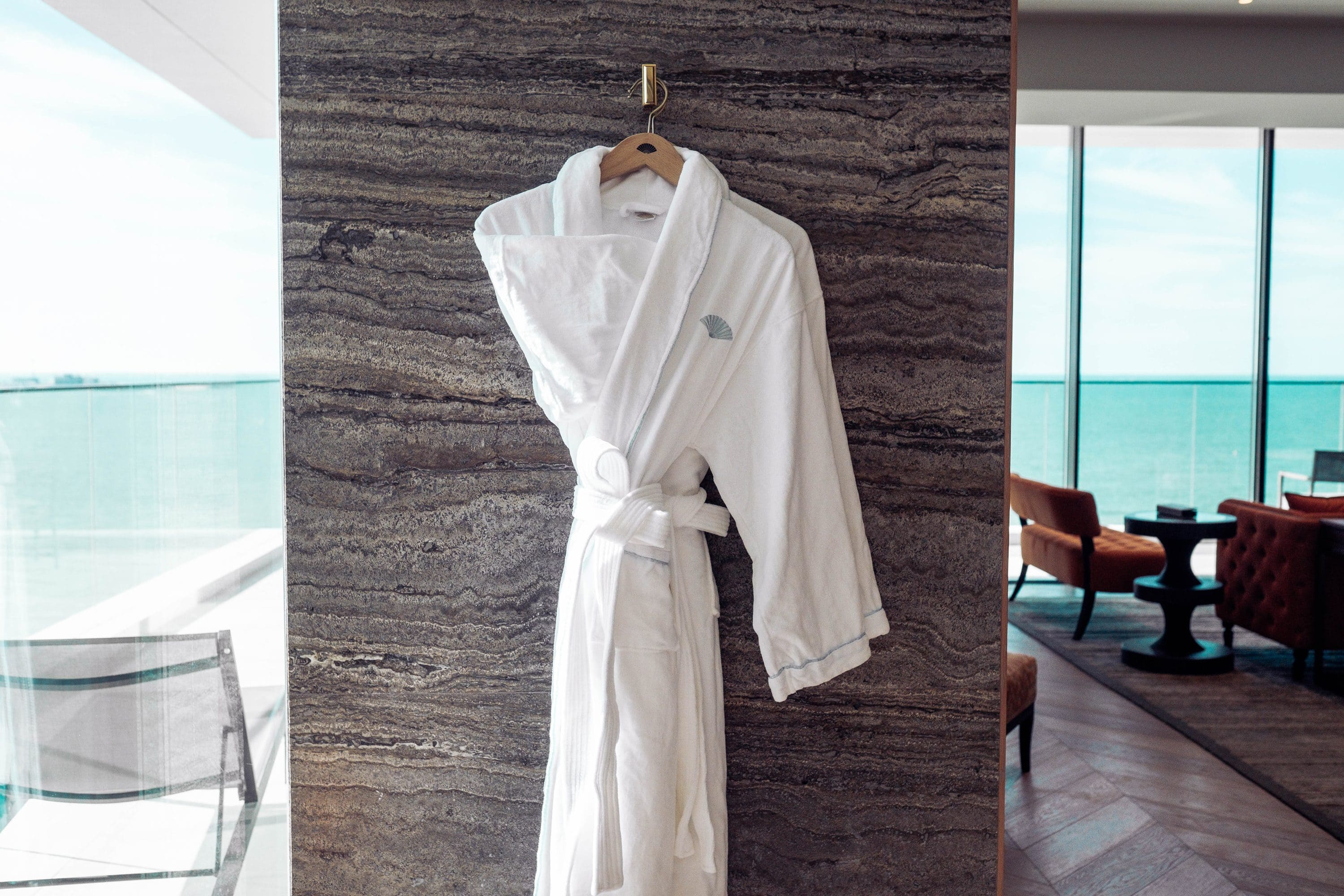 A plush bath robe hanging in the bathroom of the Seafront Suite, with views looking out onto the water beyond