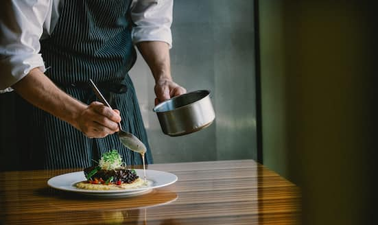 Chef plates up a dish at Amity & Commerce