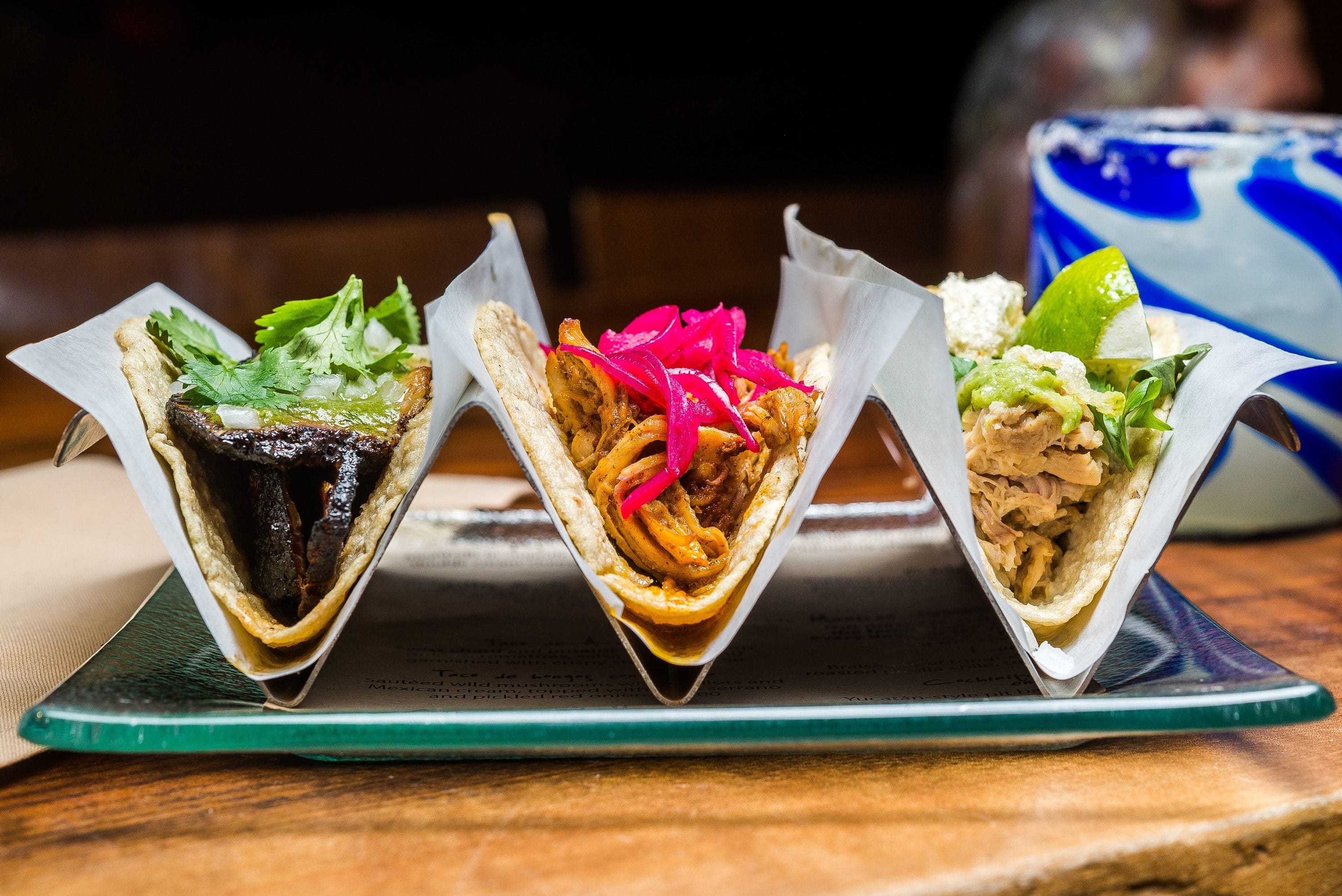 Three tacos in a rack with bright toppings