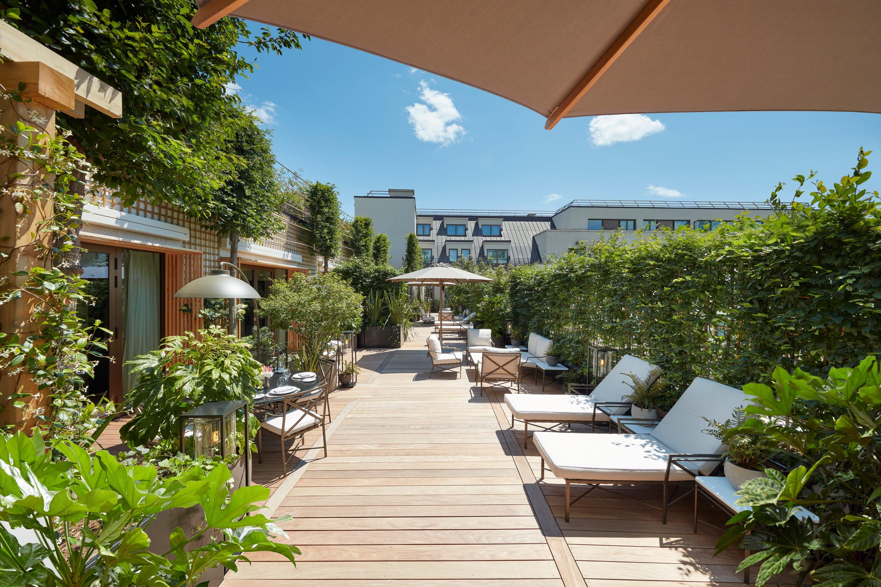 The leafy terrace of The Parisian Suite with sun loungers