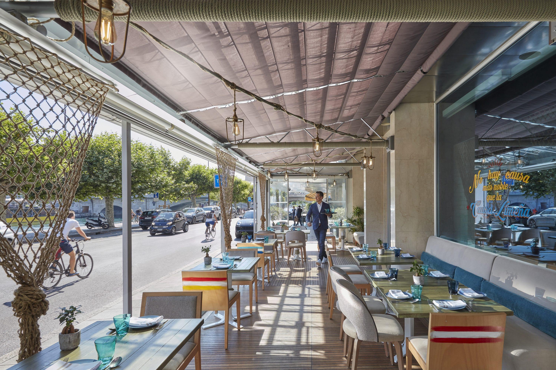 A waiter walks past tables set up for outdoor dining at Yakumanka, Geneva