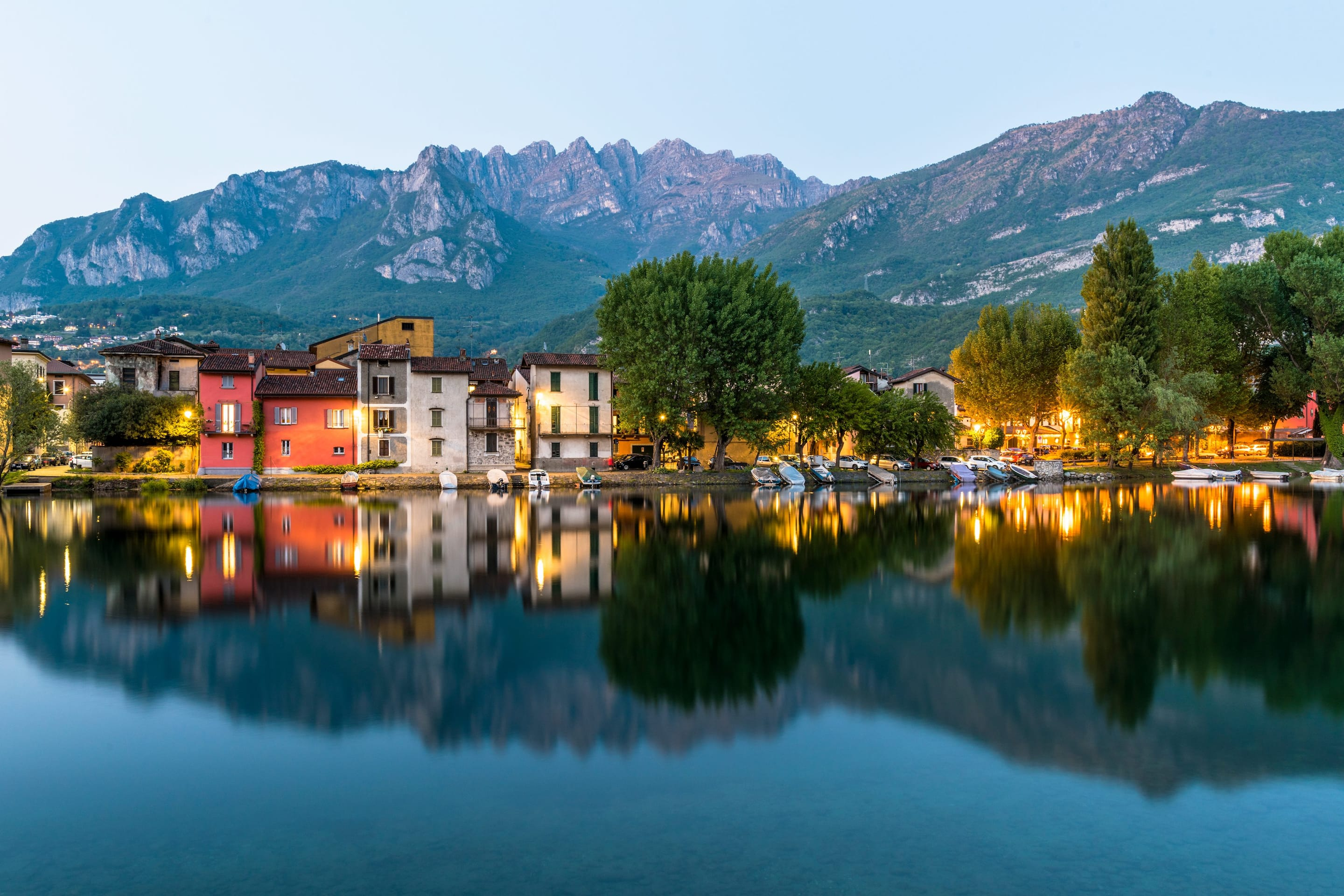 Street lights illuminate colourful buildings and trees along Lake Como