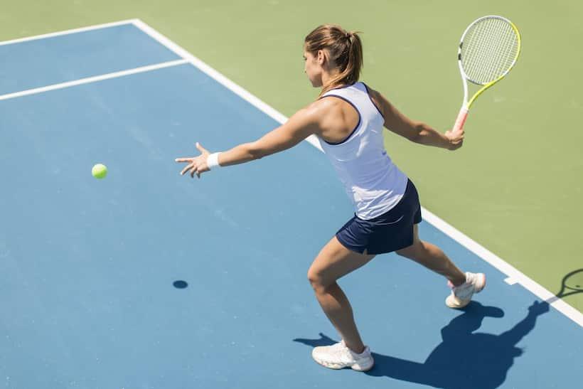 Woman hits tennis ball on a court