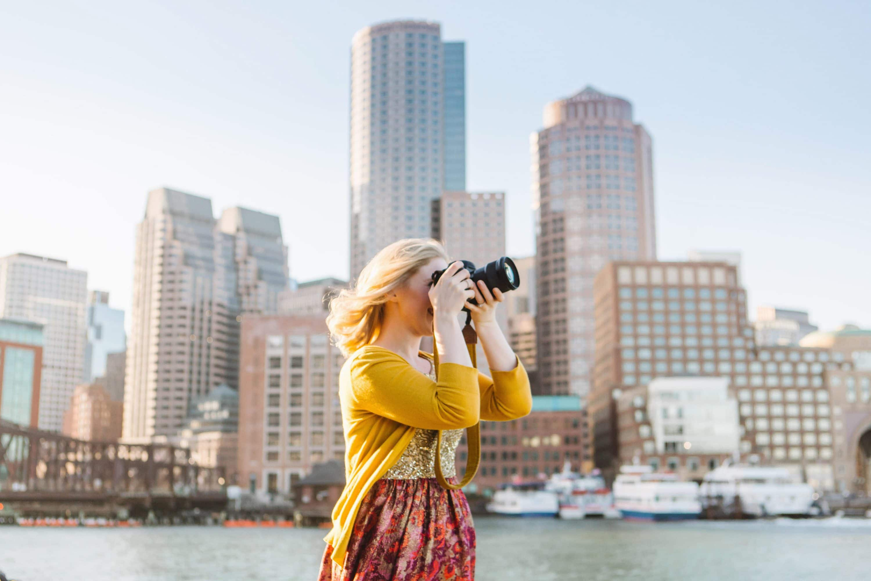 Woman takes photo with Boston backdrop