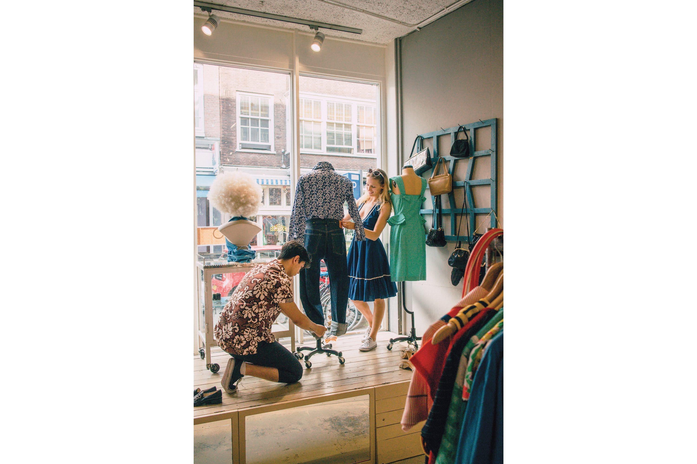 Shop assistants dress a window mannequin