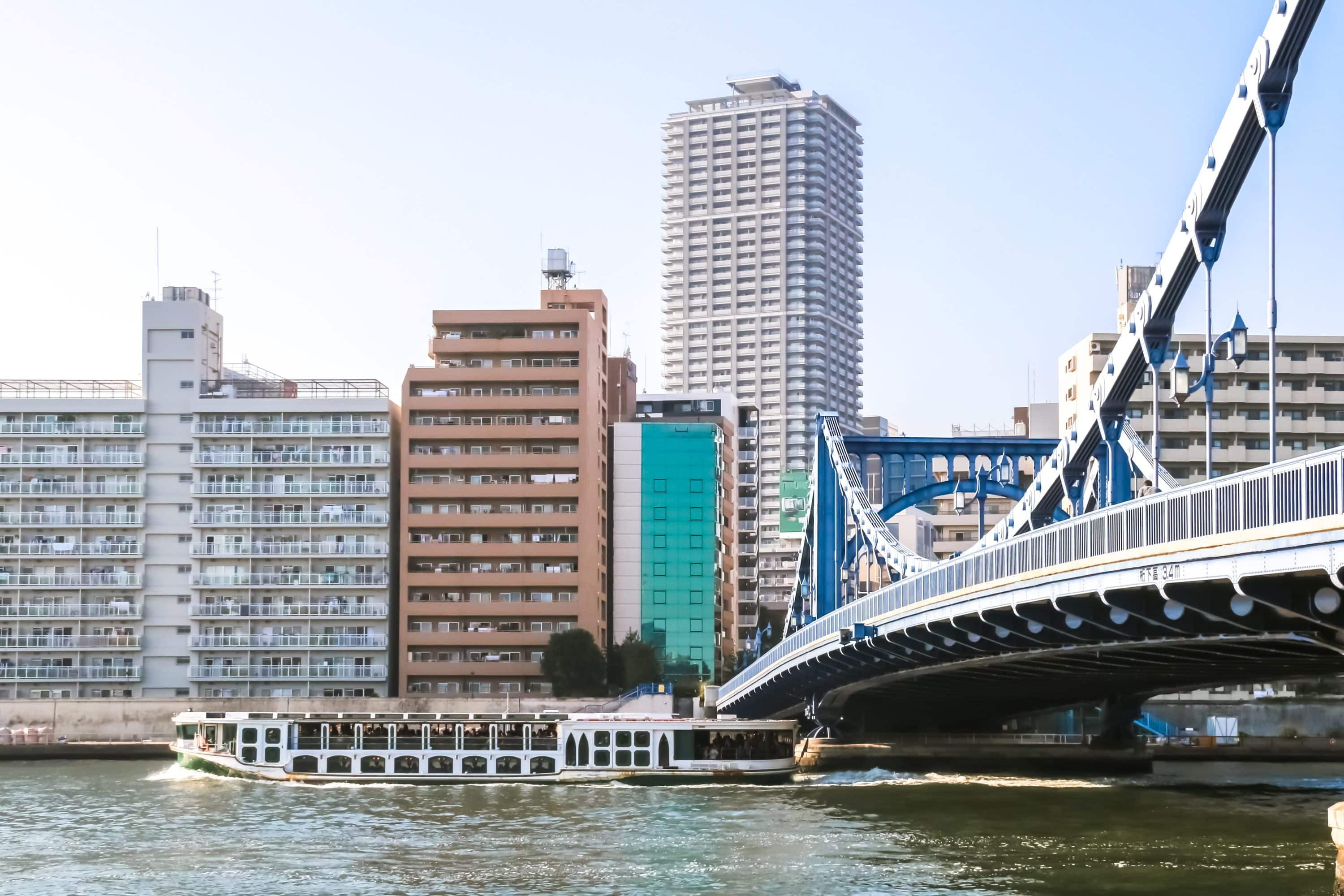 A boat emerges from under a bridge, backdropped by the Tokyo cityscape