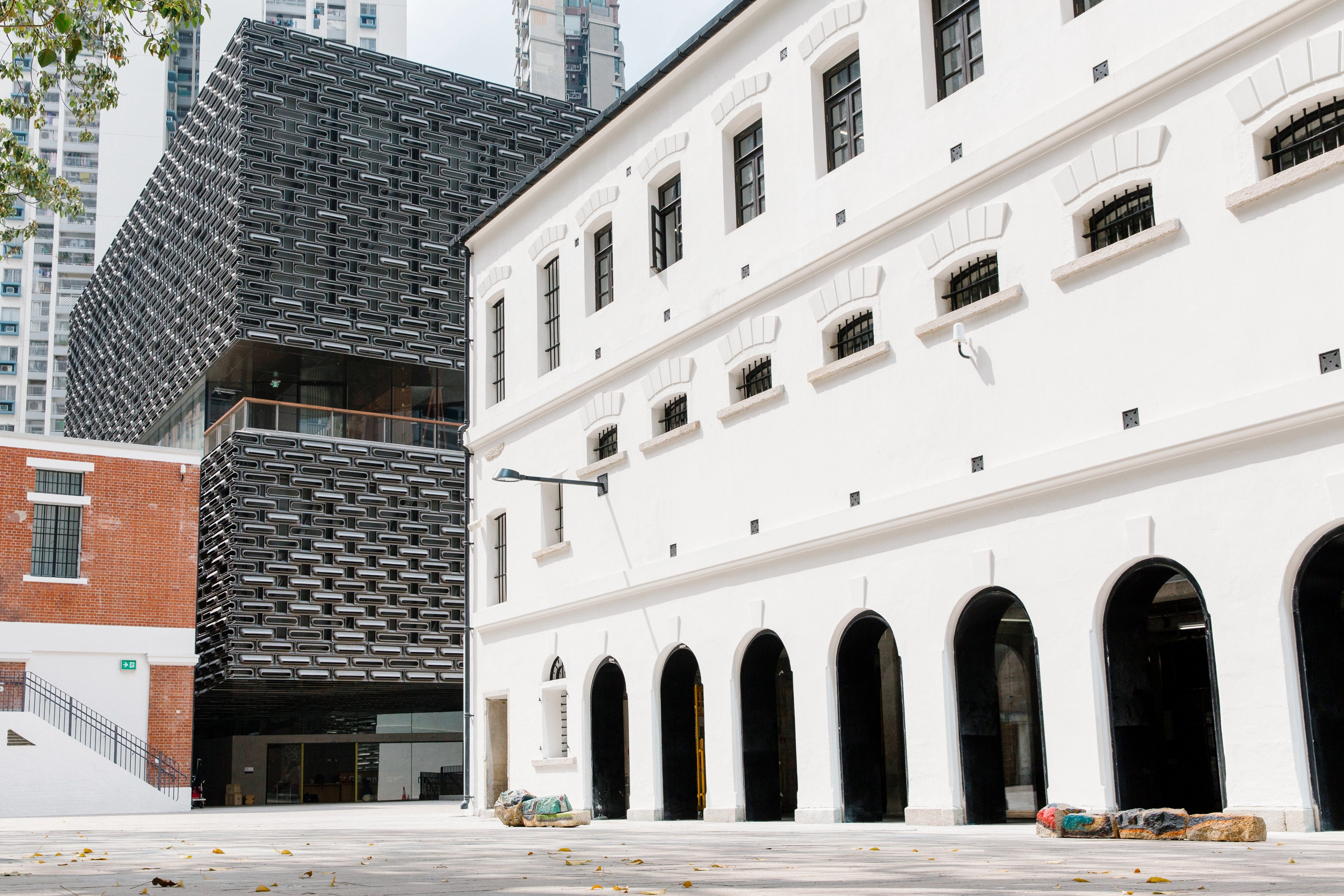 The white Victorian facade of the Tai Kwun Centre for Heritage and Arts with a modern black and grey building behind