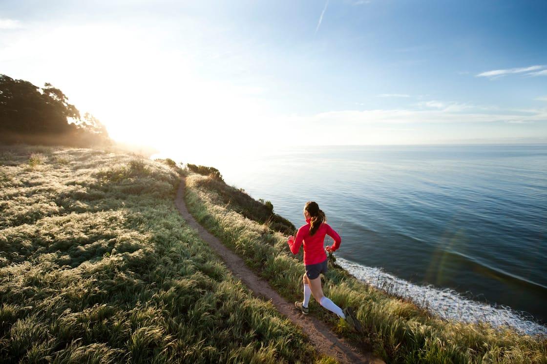 Woman runs along coastal path