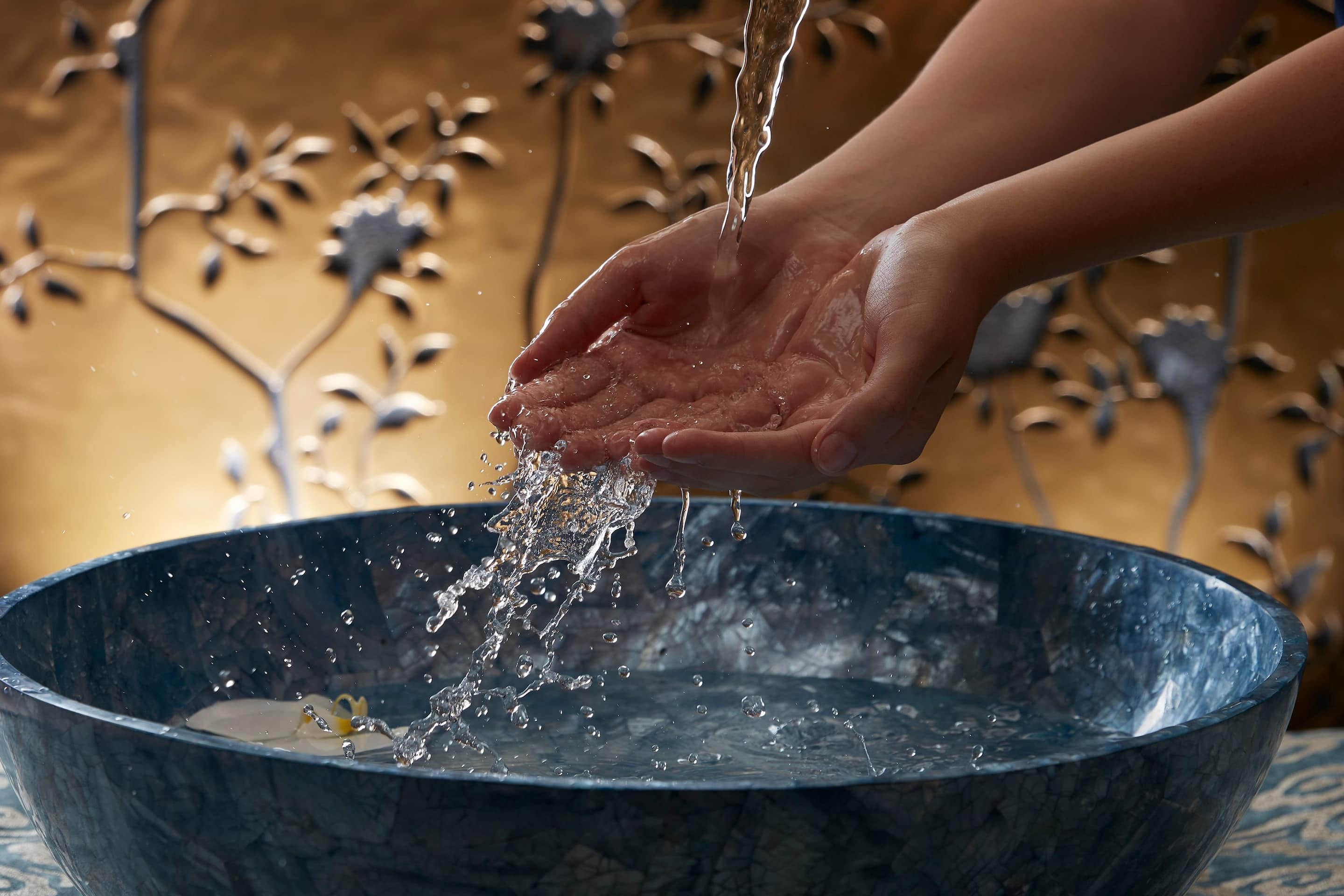 Hands in a bowl of water as part of a spa treatment at Mandarin Oriental Hyde Park