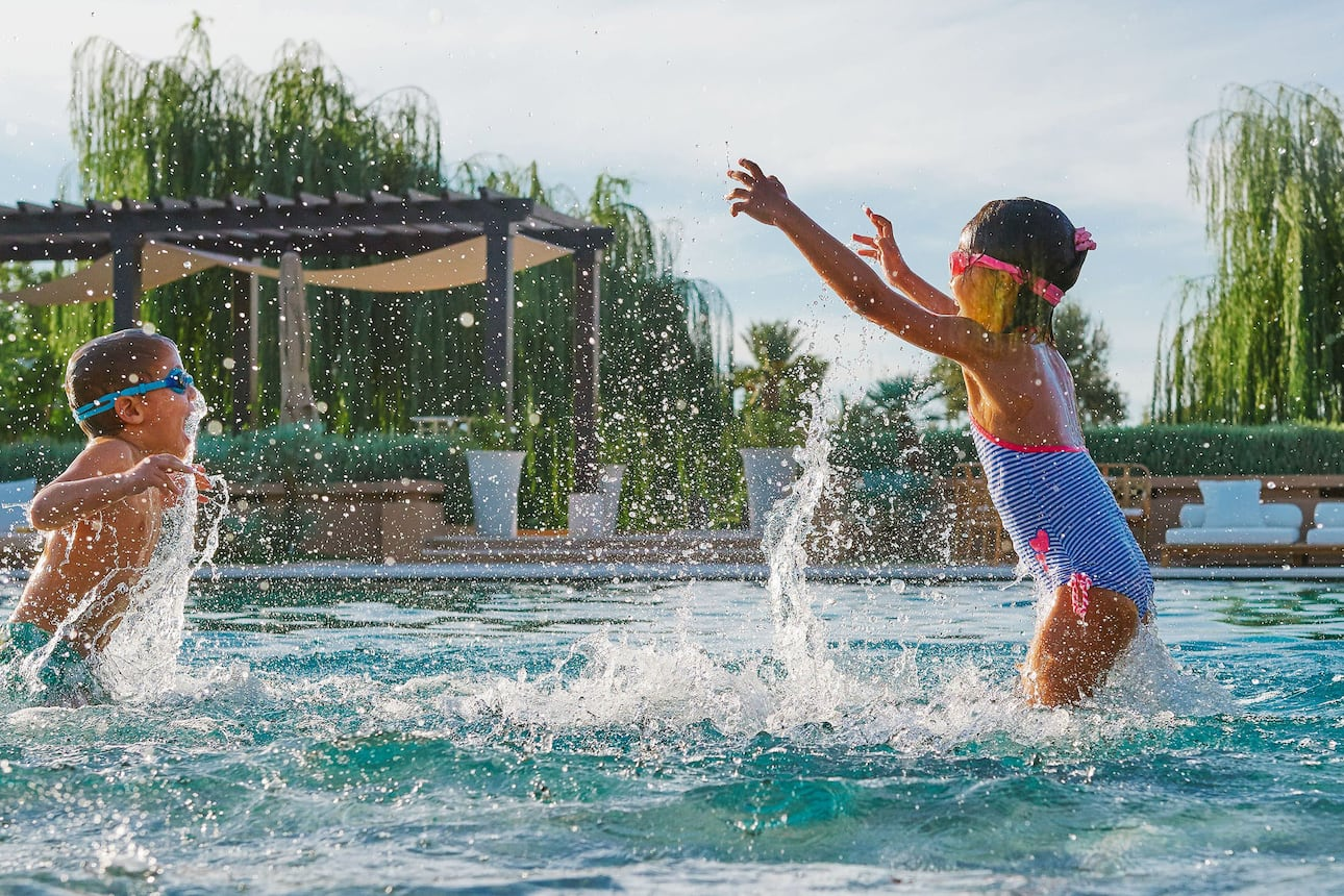Two children splash about in the swimming pool at Mandarin Oriental, Marrakech