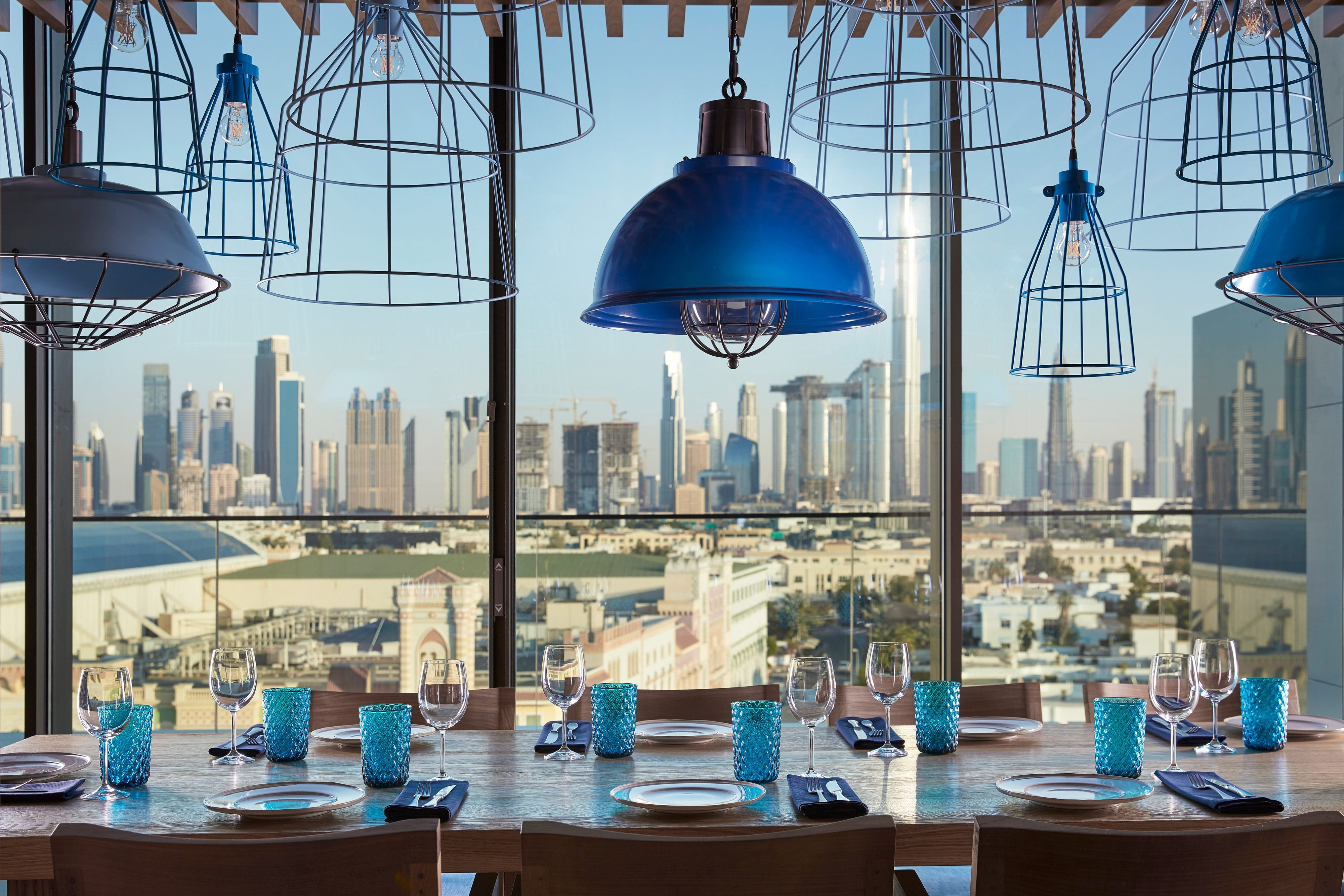 View from the city-view tables at Tasca restaurant at Mandarin Oriental Jumeira, Dubai with its blue handing lights and blue water glasses