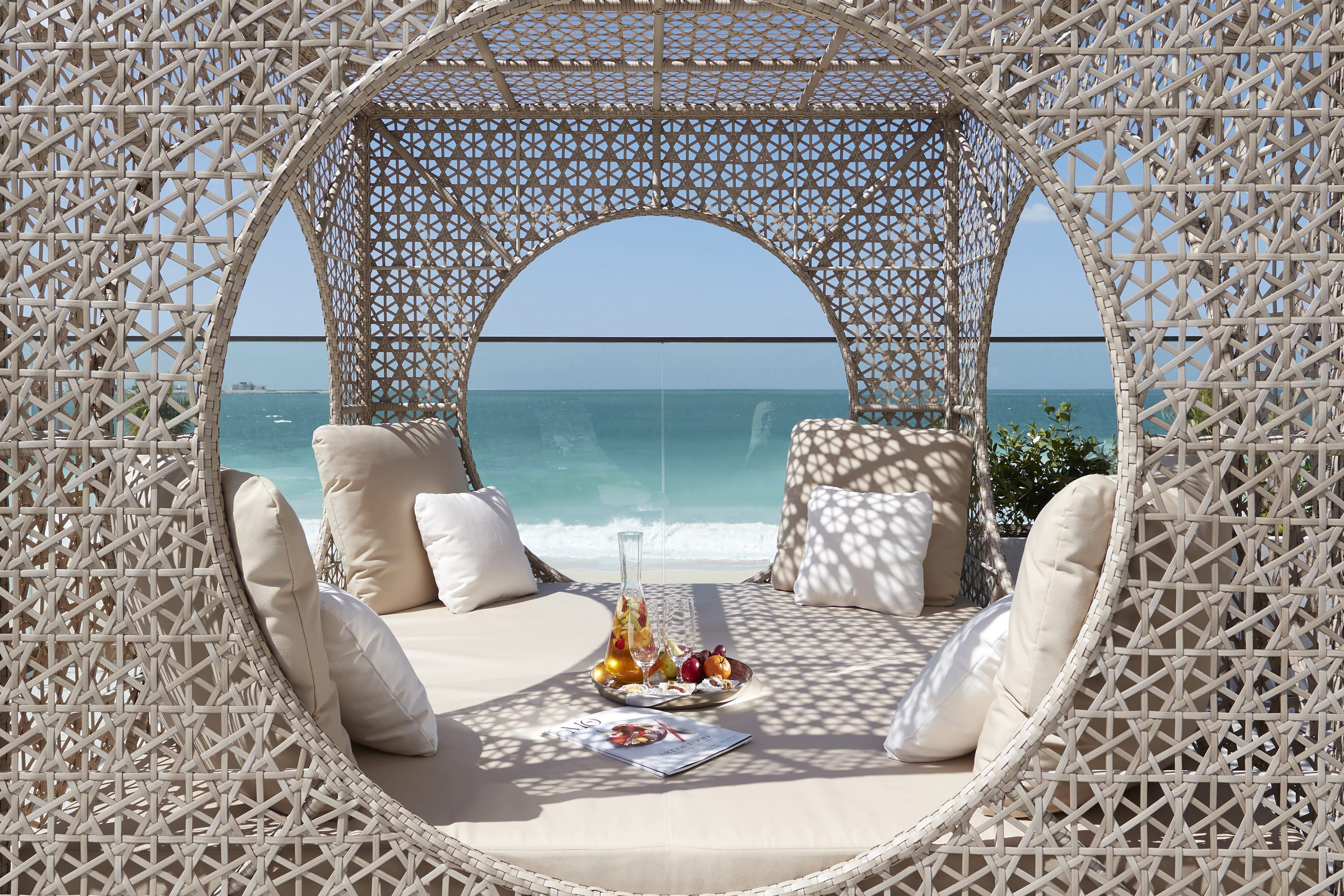 Fruit and water on a plush daybed with views of the Arabian Sea in the background