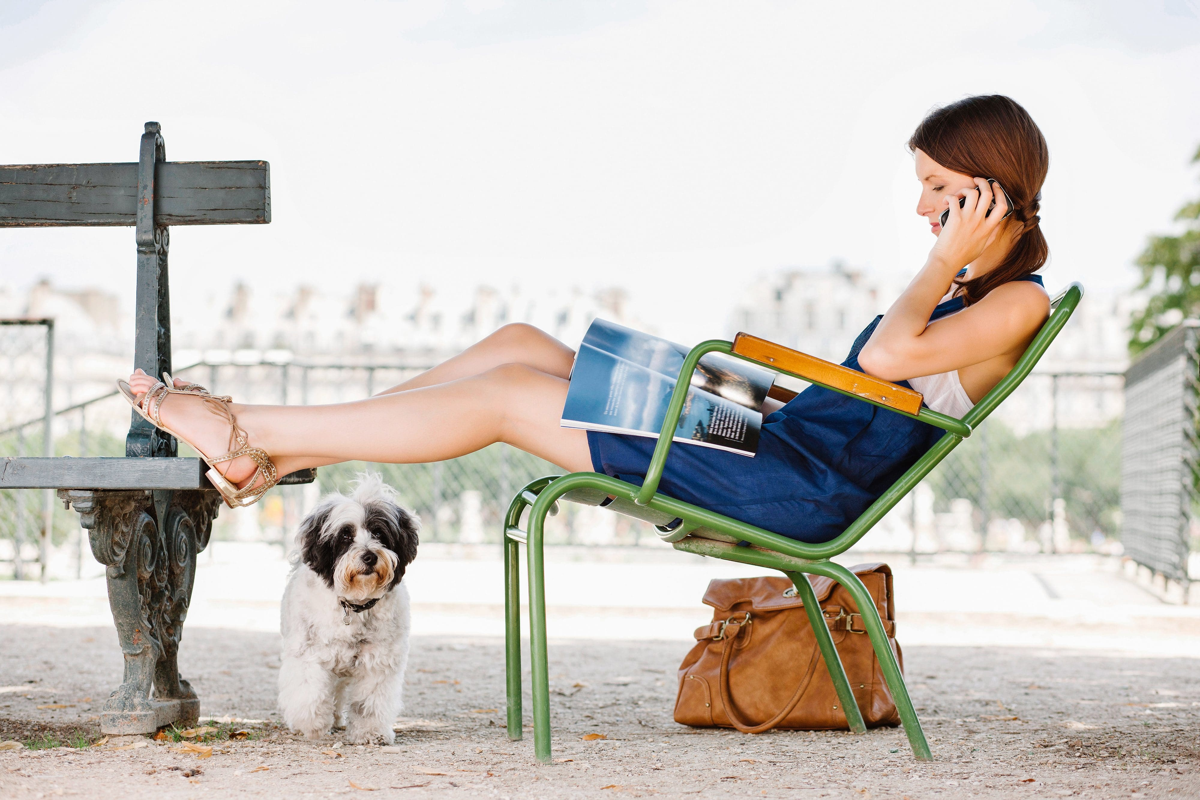 Dog walker relaxing on a bench in a Paris park while her dog stands under her legs