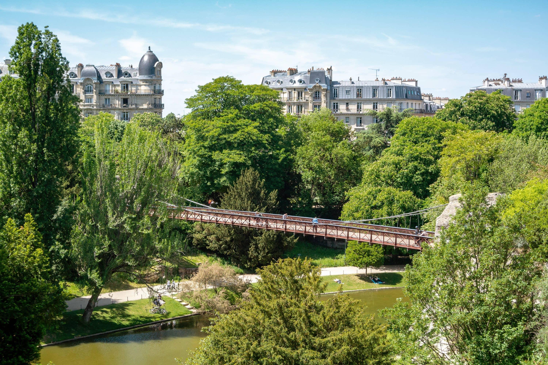 A bridge over water in leafy Parc des Buttes Chaumont, Paris
