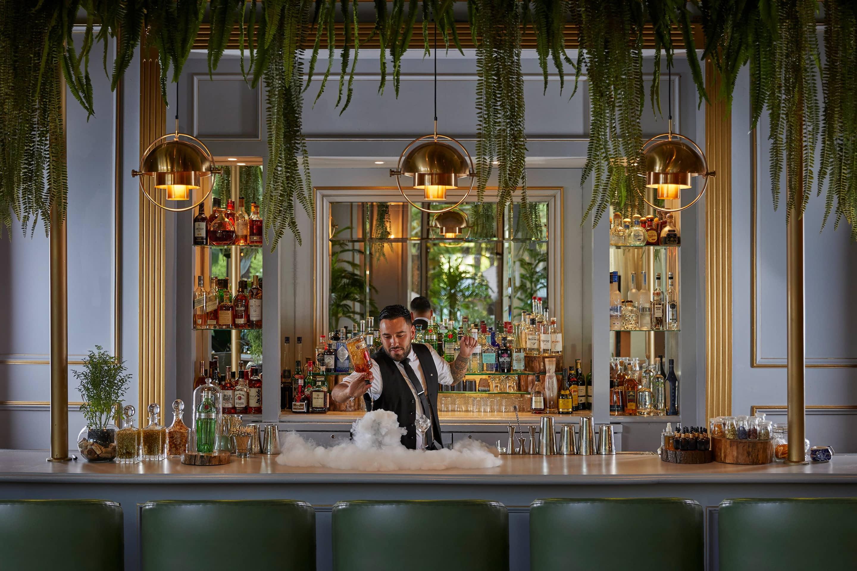 Bartender prepares a drink at Origen Bar