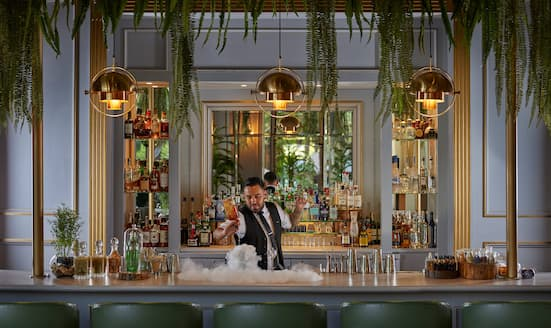 Bartender mixes cocktails behind bar