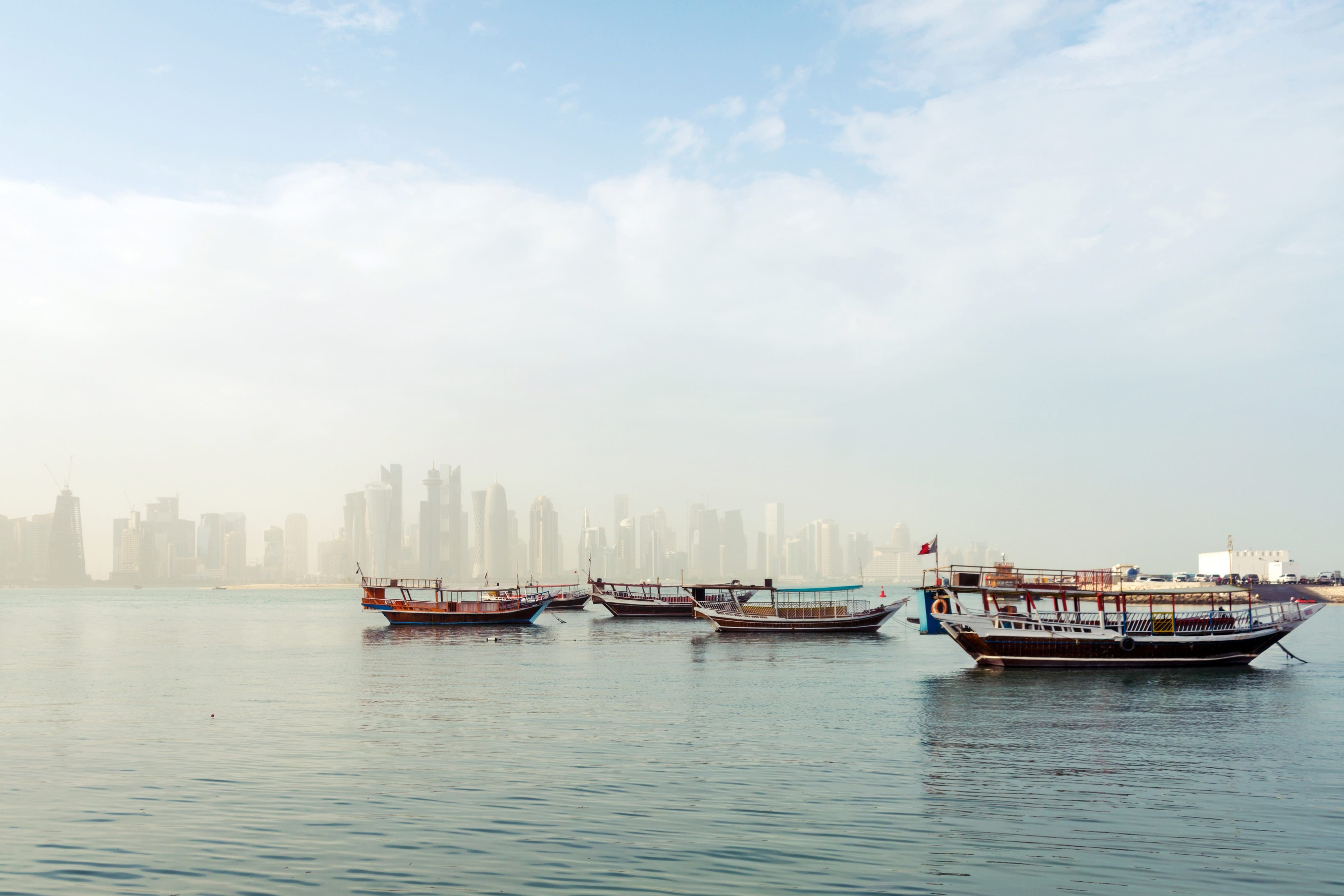 Wooden dhows on the Arabian sea, backdropped by the Doha skyline
