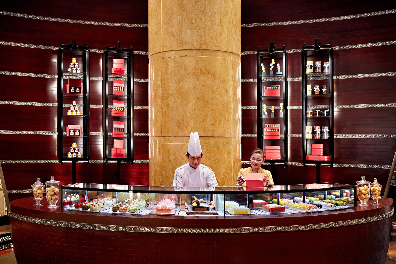 Sweet treats surround workers in The Mandarin Cake Shop, Kuala Lumpur