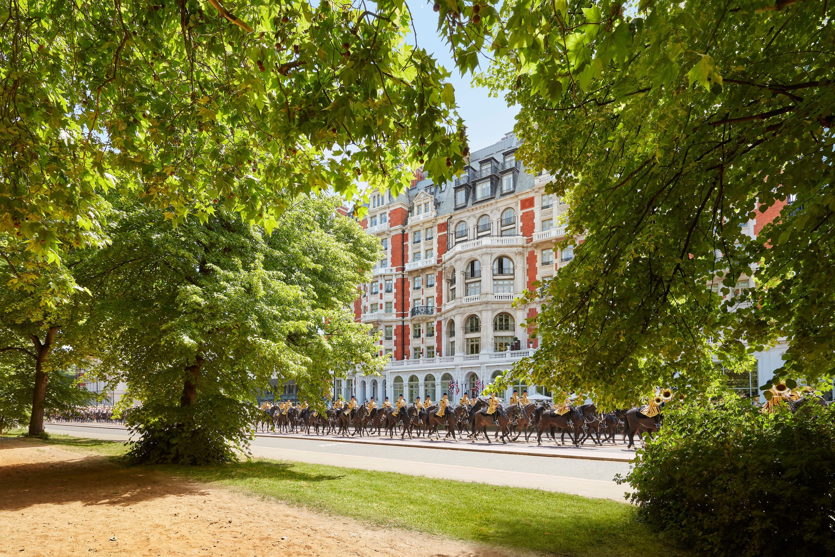 Exterior of Mandarin Oriental Hyde Park, London with guards on horses passing by