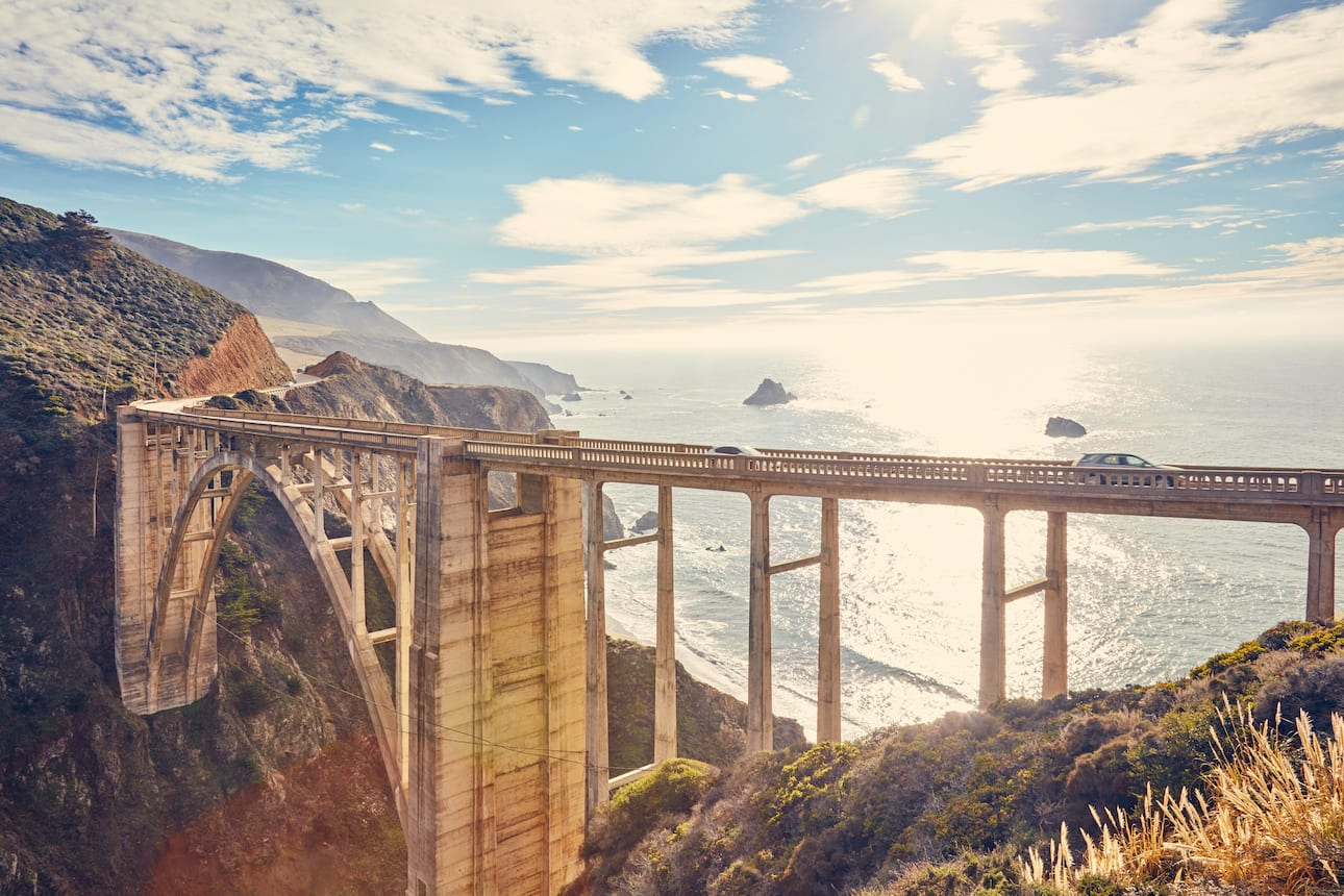 Cars motor along Bixby Creek Bridge on the Big Sur coast of California
