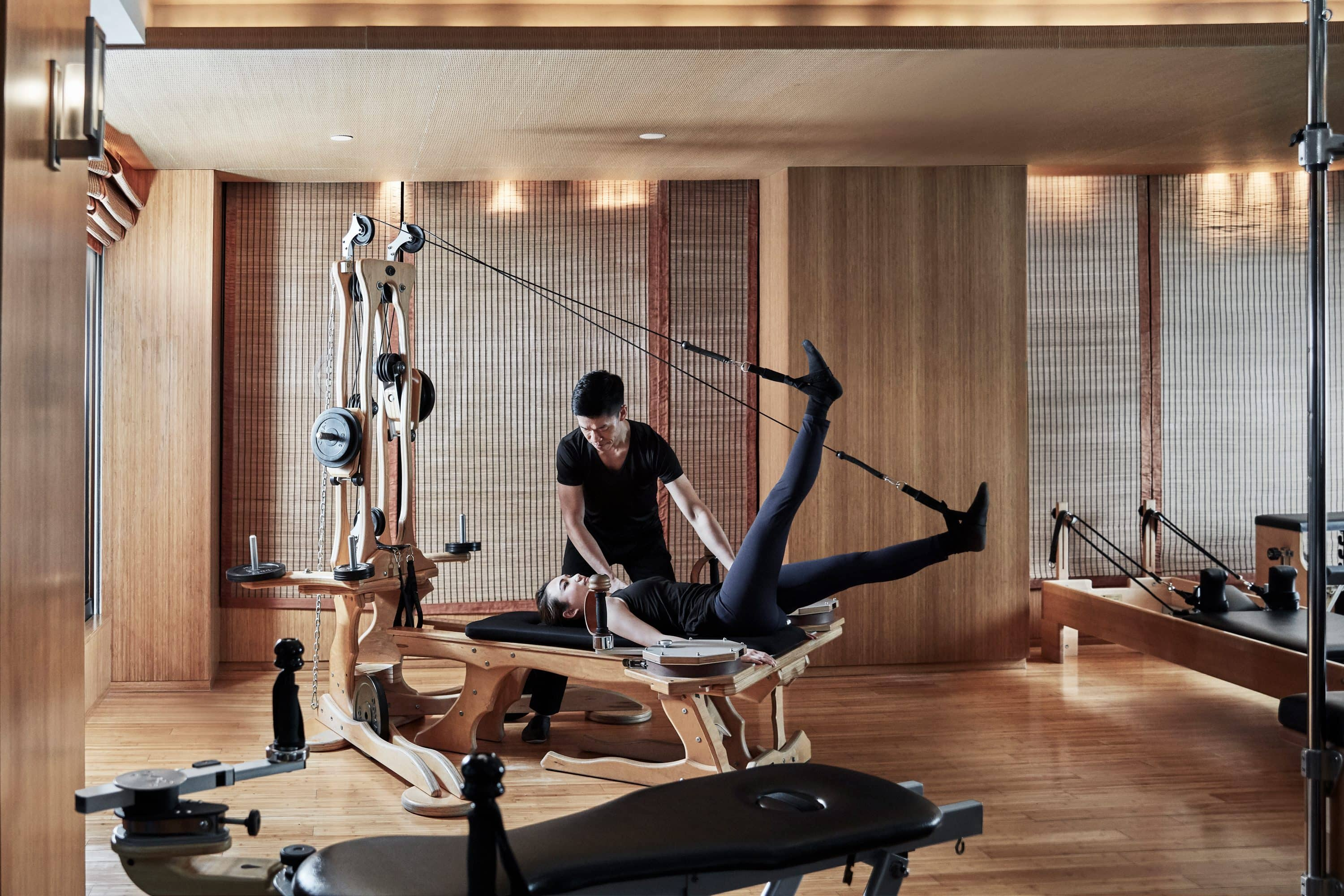 A guest exercising with a trainer in the gym