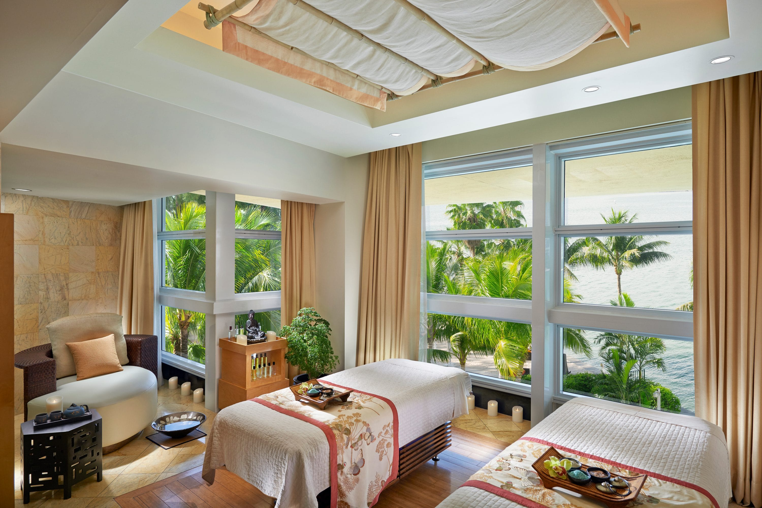 A luxury spa couples suite overlooking palm trees and water
