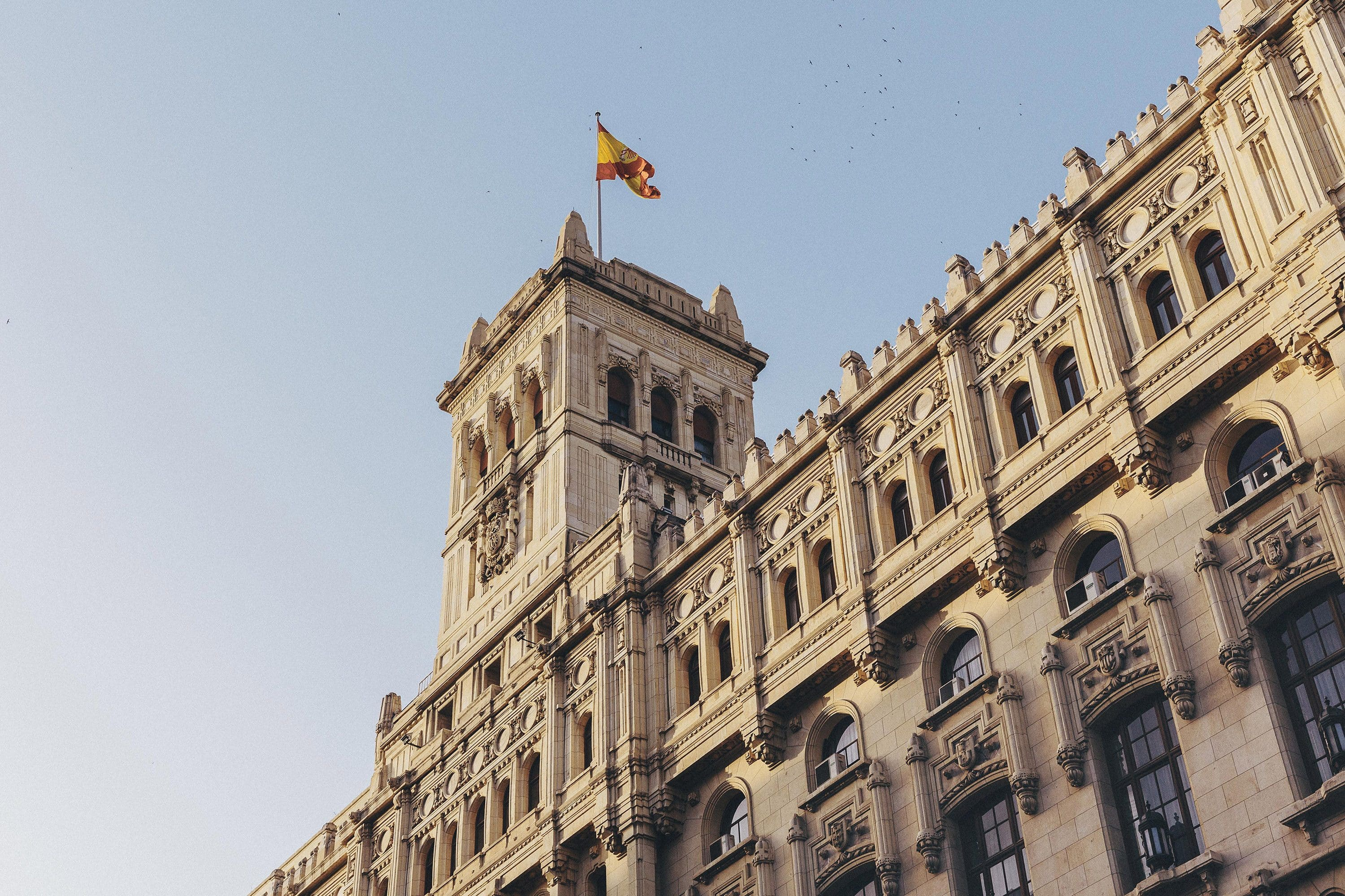 Palacio de Cibeles, Madrid with a Spanish flag blowing in the wind