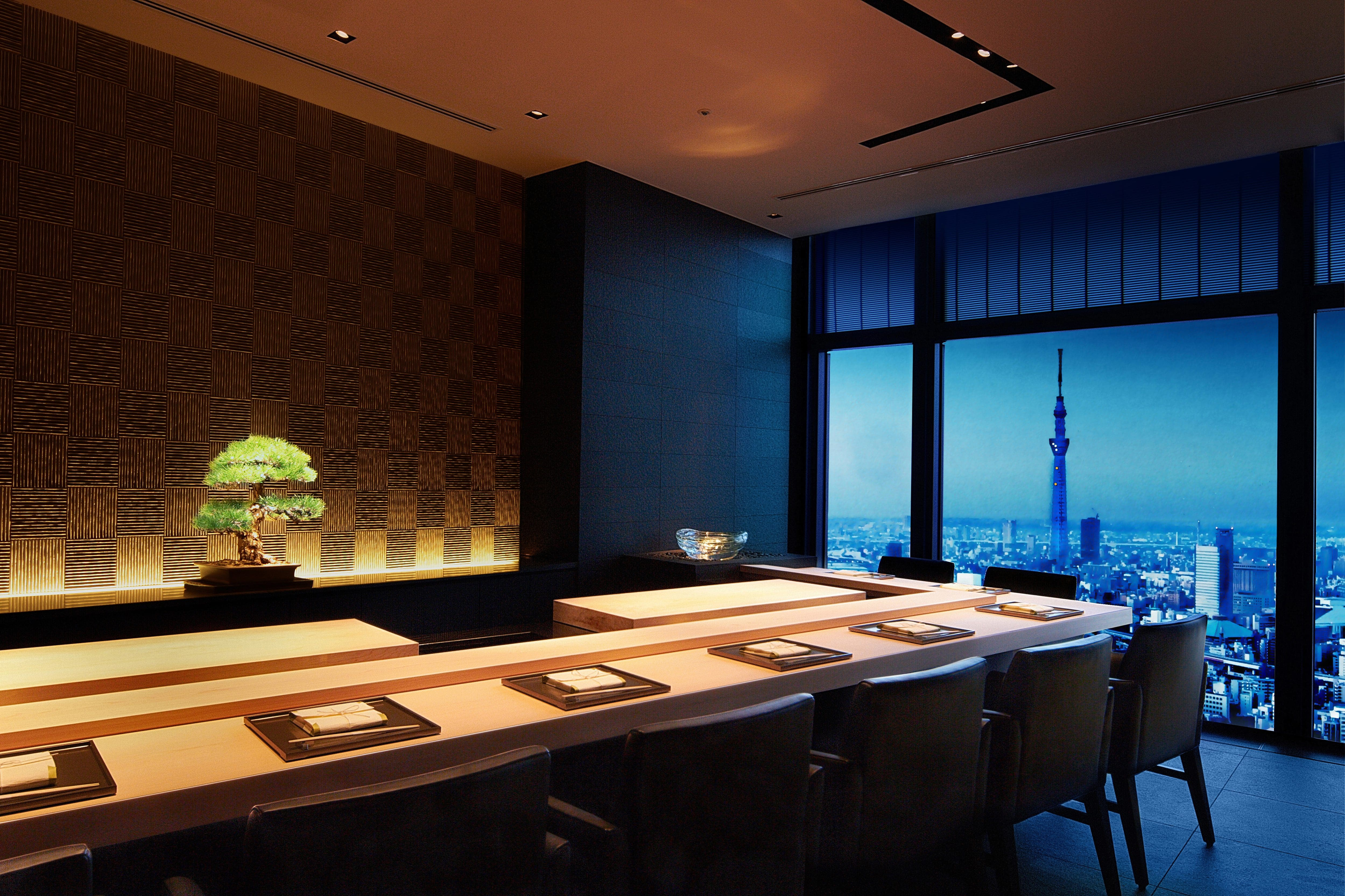 The kitchen counter table laid ready for evening service at Sushi Sora, with views overlooking the Tokyo skyline