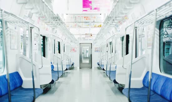 Looking down a bright white carriage of a Tokyo Metro train