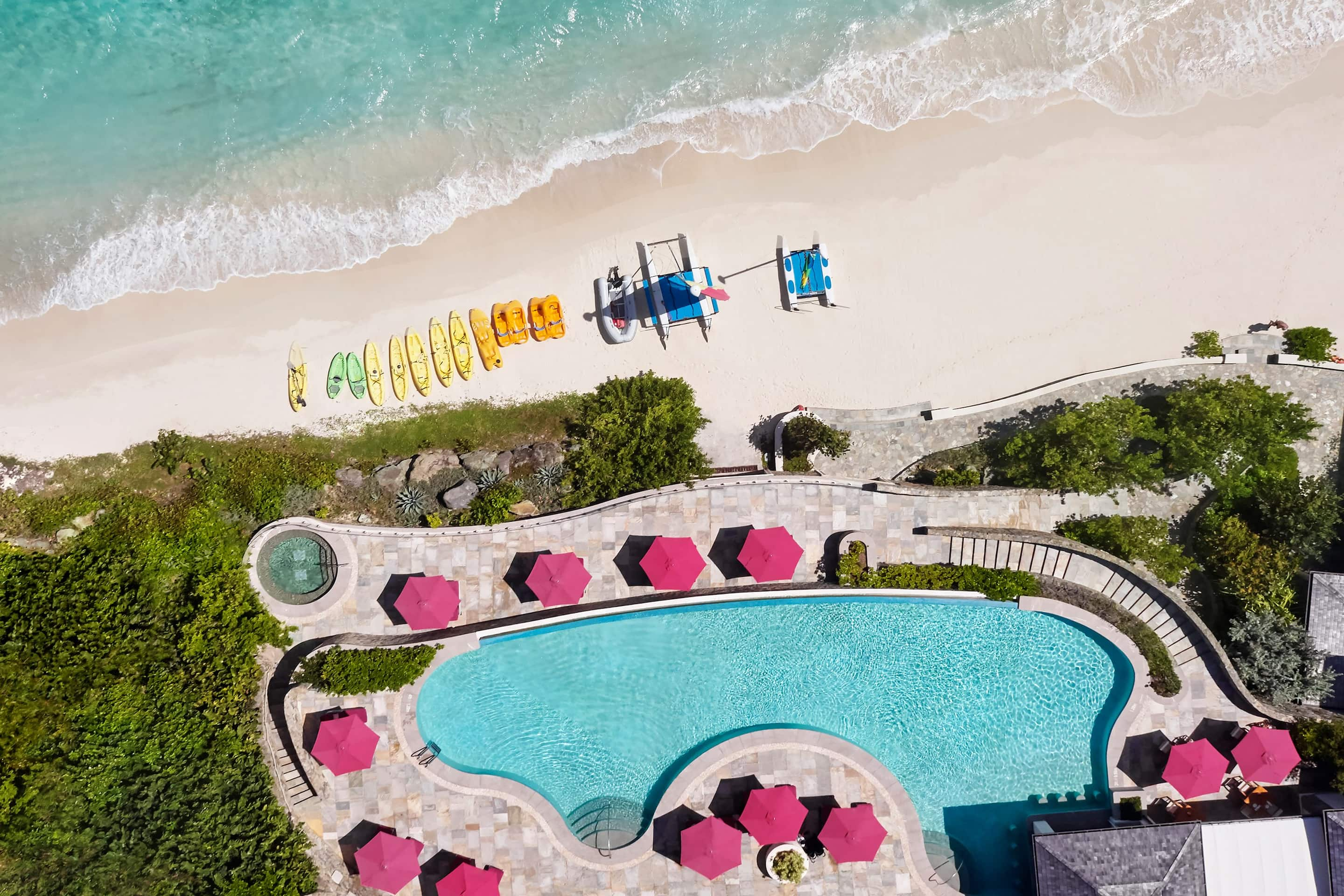 Aerial shot of the pool and canoes lined up on the beach at Mandarin Oriental, Canouan