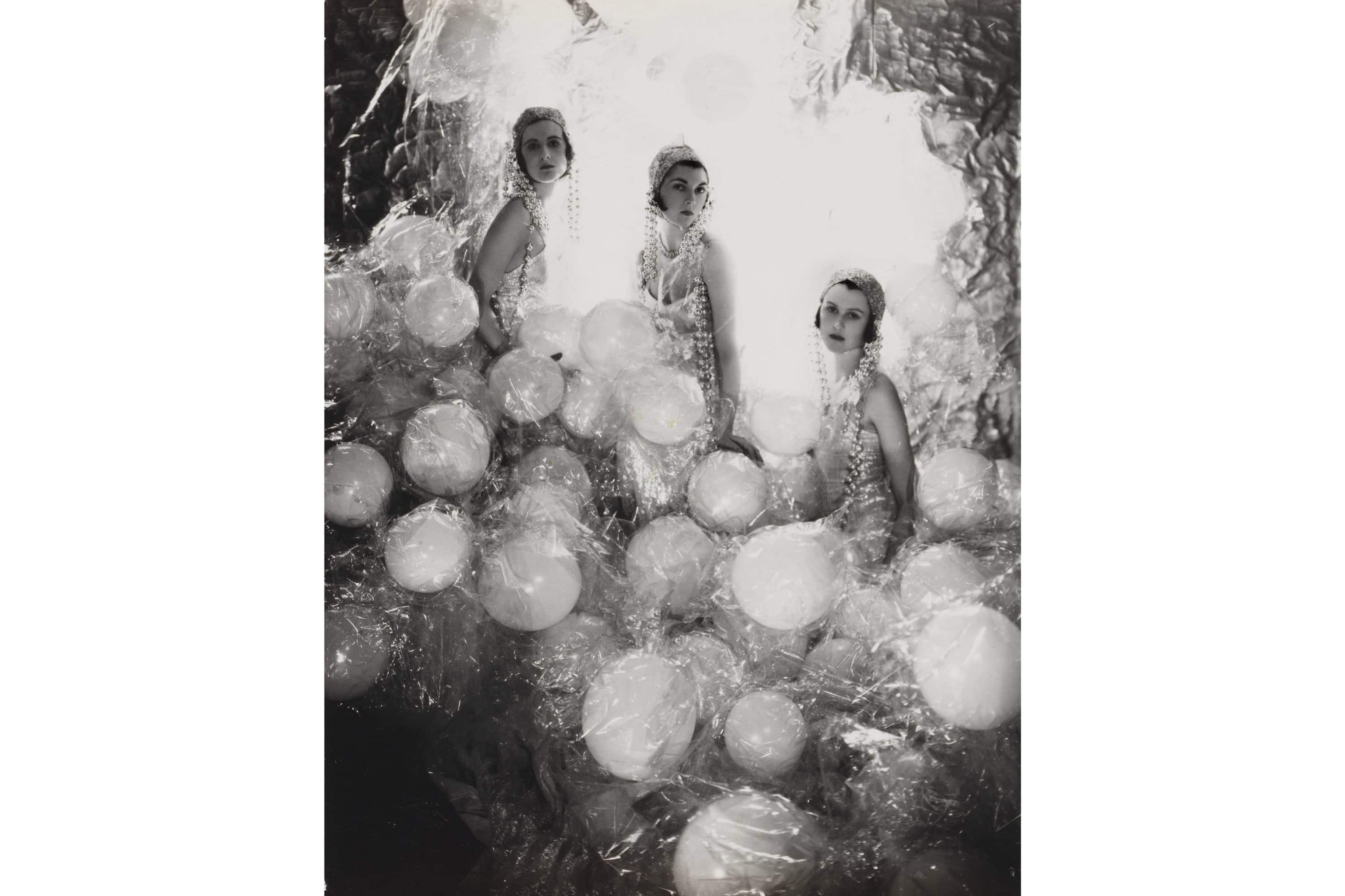 Three women pose with balloons in a Cecil Beaton photograph