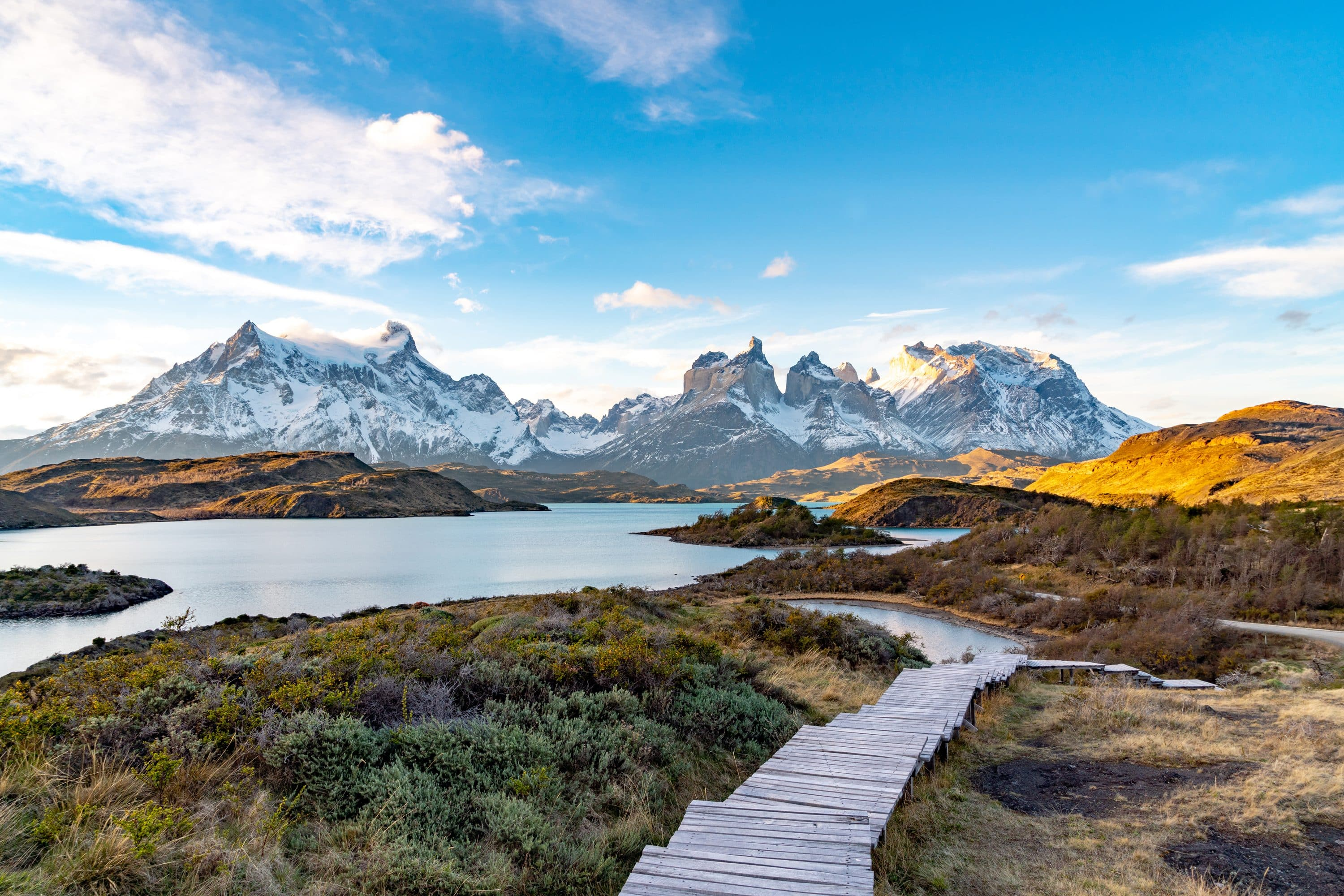 Snow-capped mountains backdrop a winding trail at the Torres del Paine, Patagonia