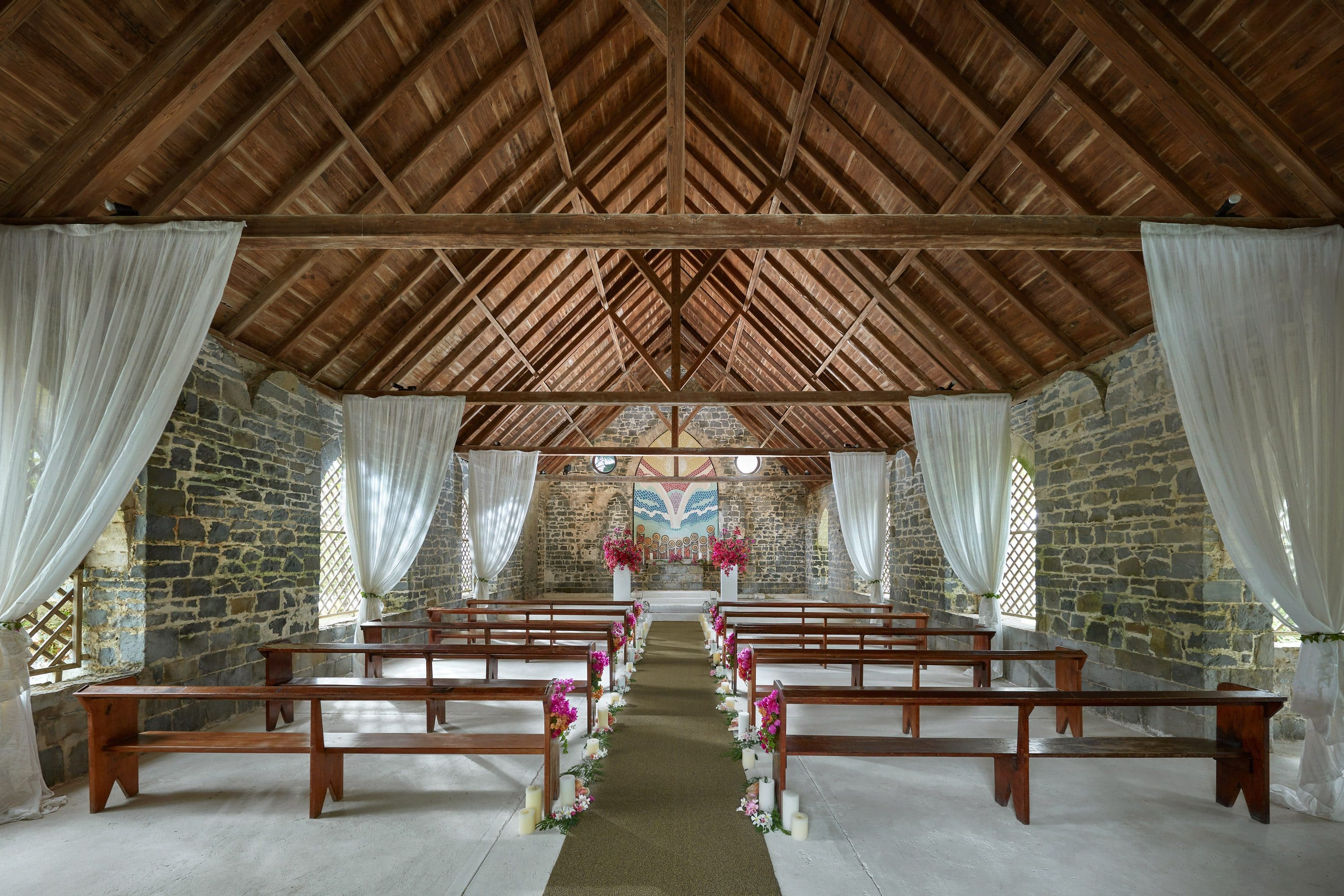Church with vaulted ceiling set ready for a wedding with flowers on the pews in Canouan