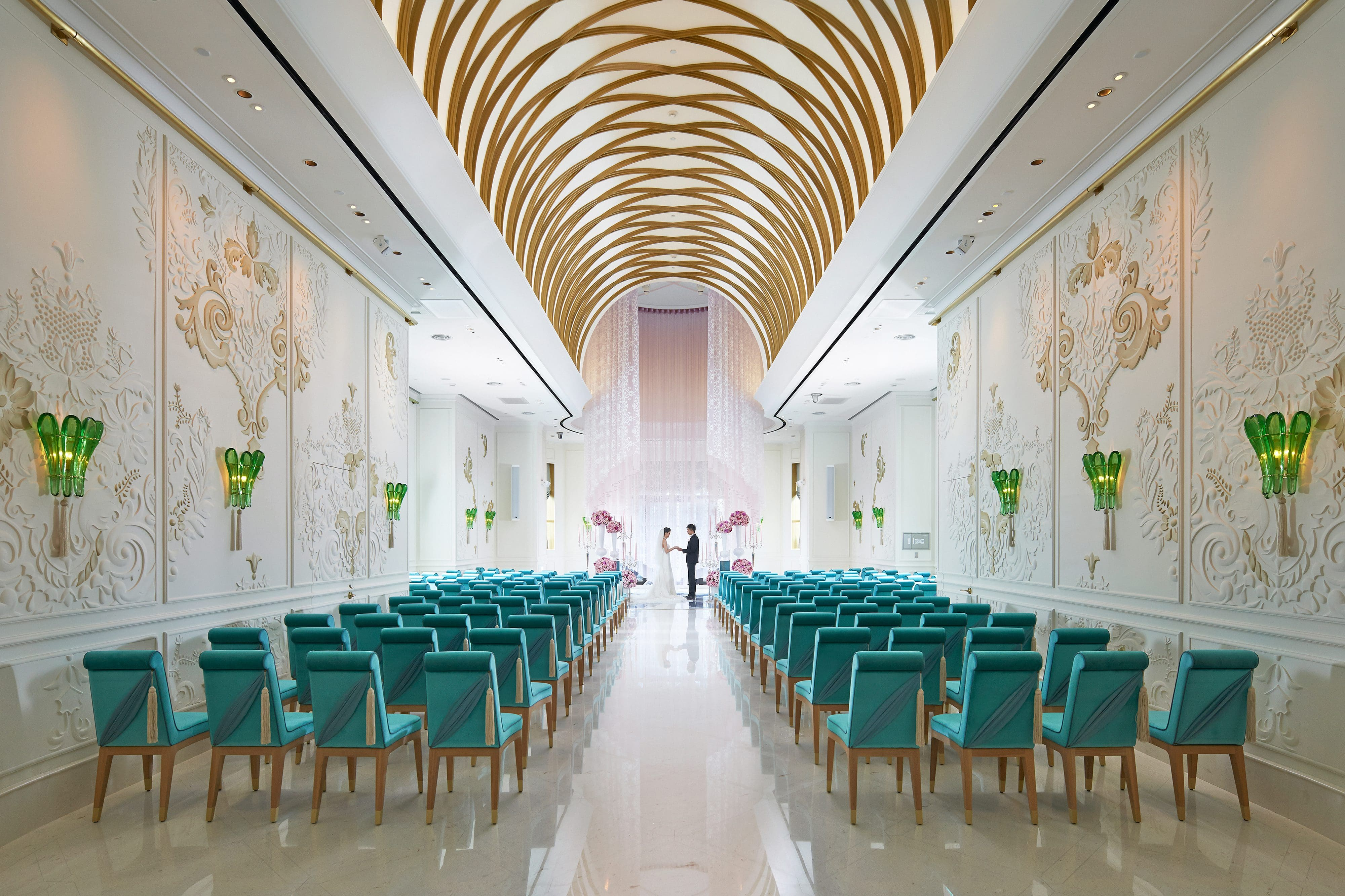 View down the aisle at a couple getting married at the vaulted chapel room at Mandarin Oriental, Taipei