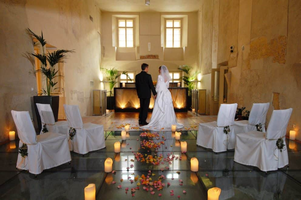 Bride and groom hold hands in an intimate candle-lit venue at Mandarin Oriental, Prague