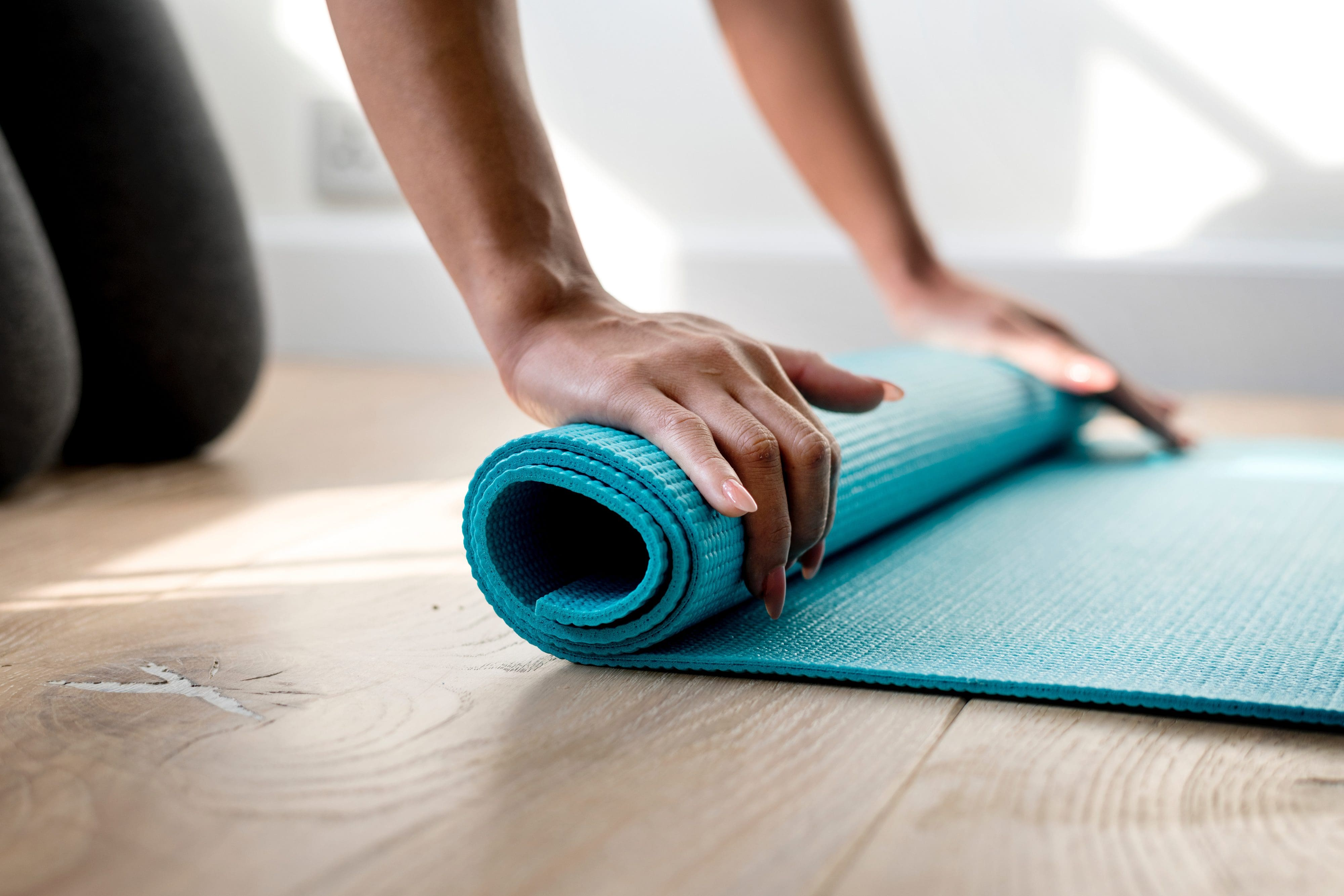 Person rolls up a yoga mat
