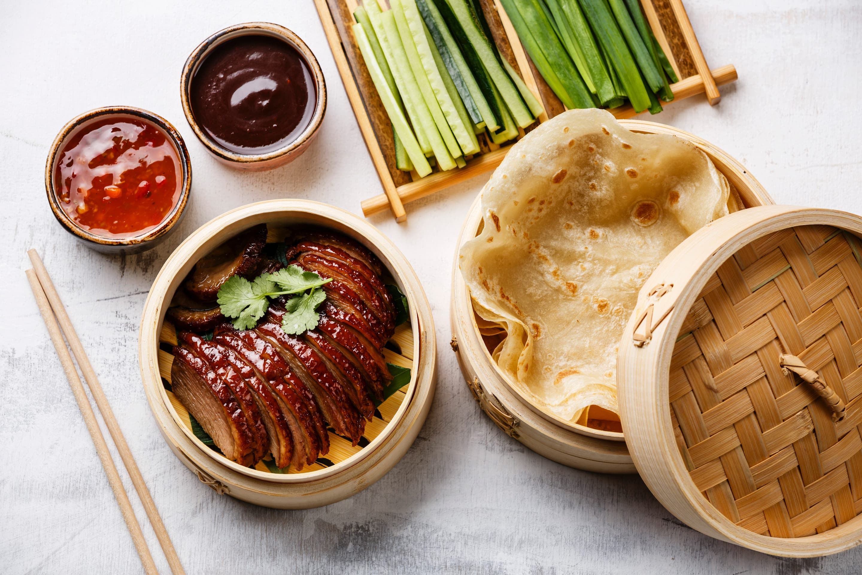 Sliced peking duck, pancakes and plum sauce presented on a table