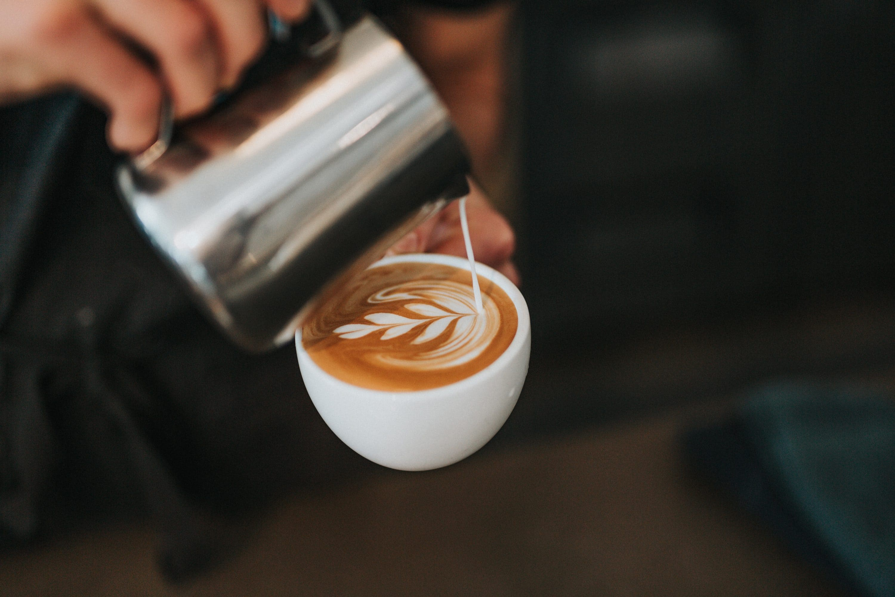 Milk being poured into a coffee