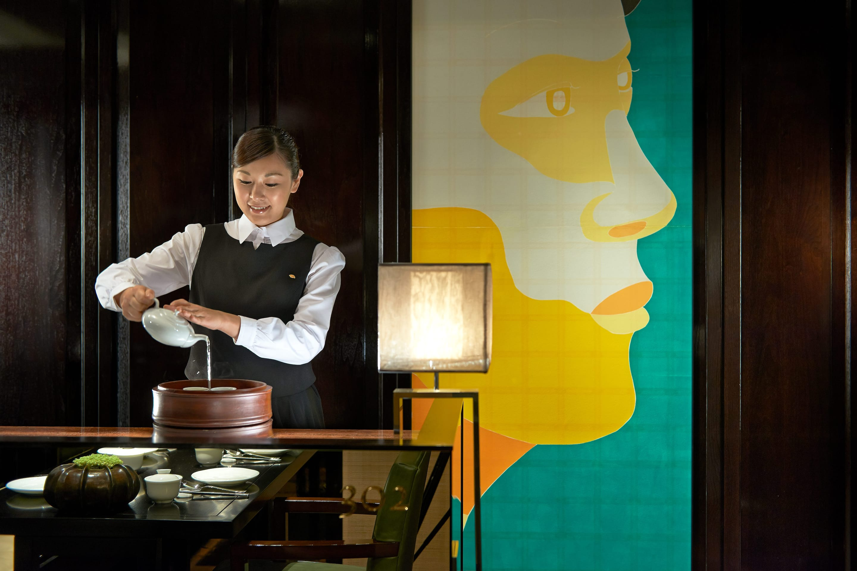 Woman pouring tea at Ye Ge at Mandarin Oriental, Taipei