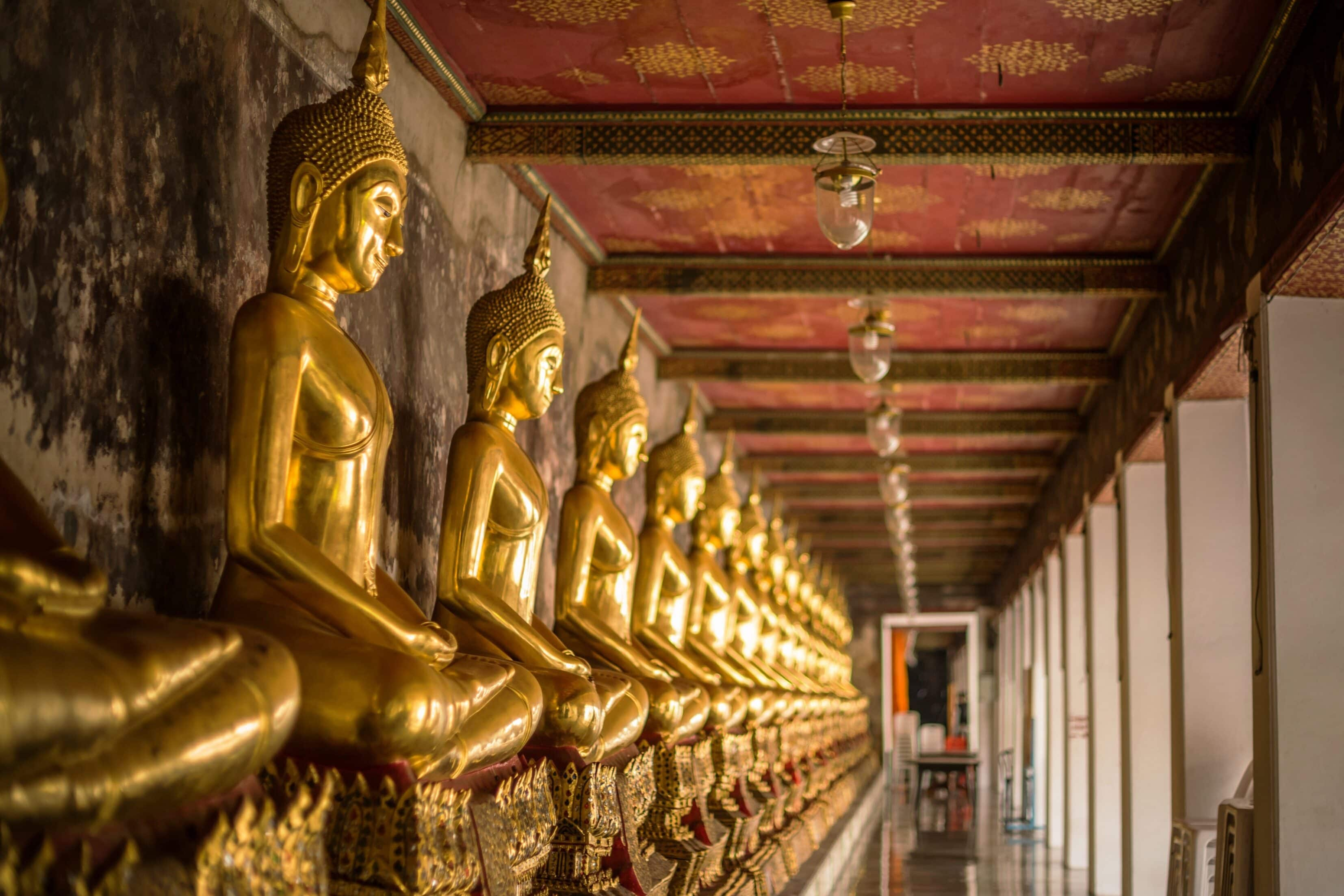 A row of golden buddhas inside a temple