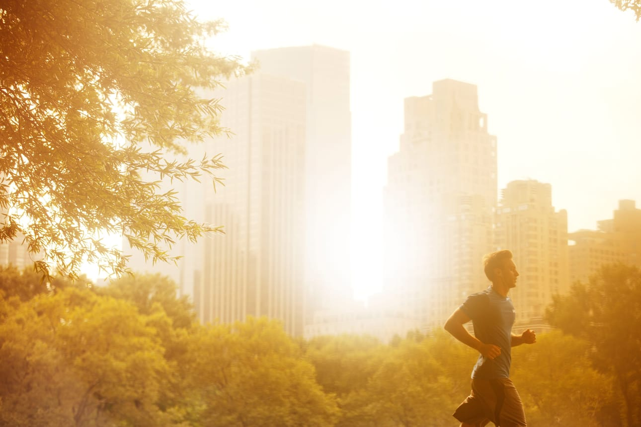 A man running at sunrise with the skyline in the background