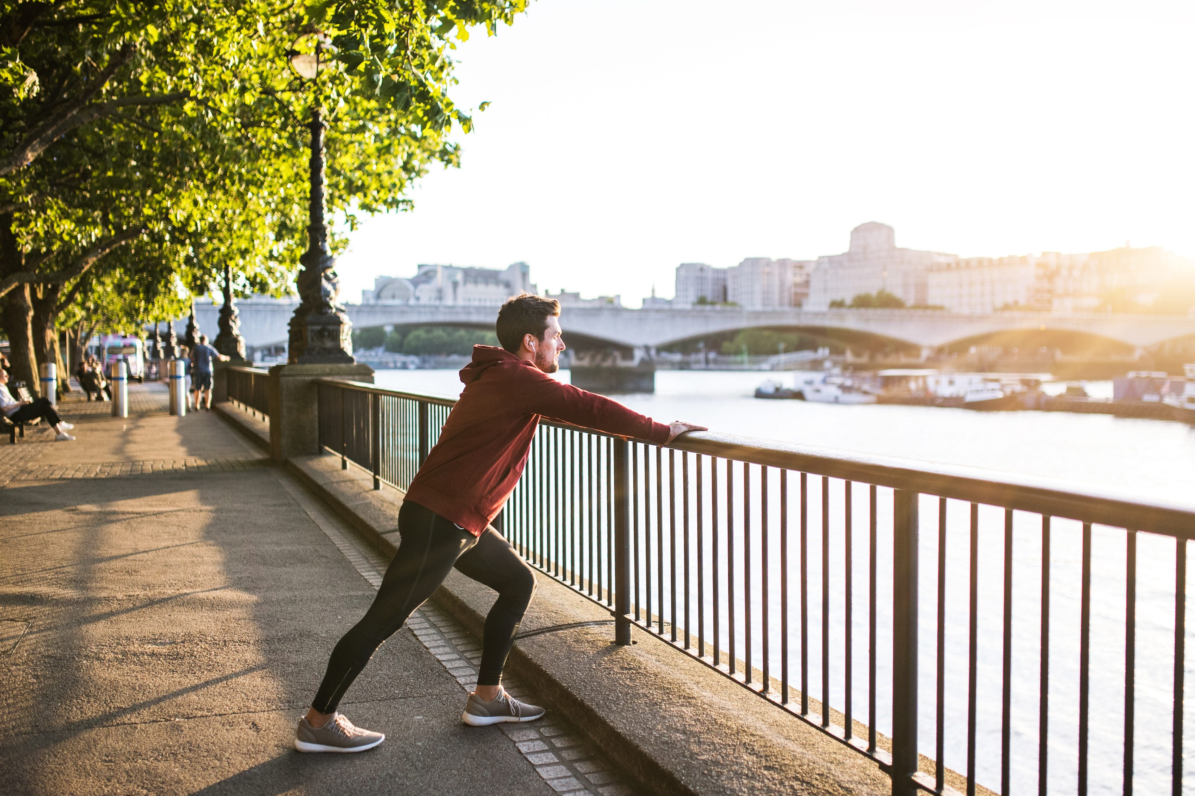 Man stretches against the balustrade of the River Thames on London's South Bank