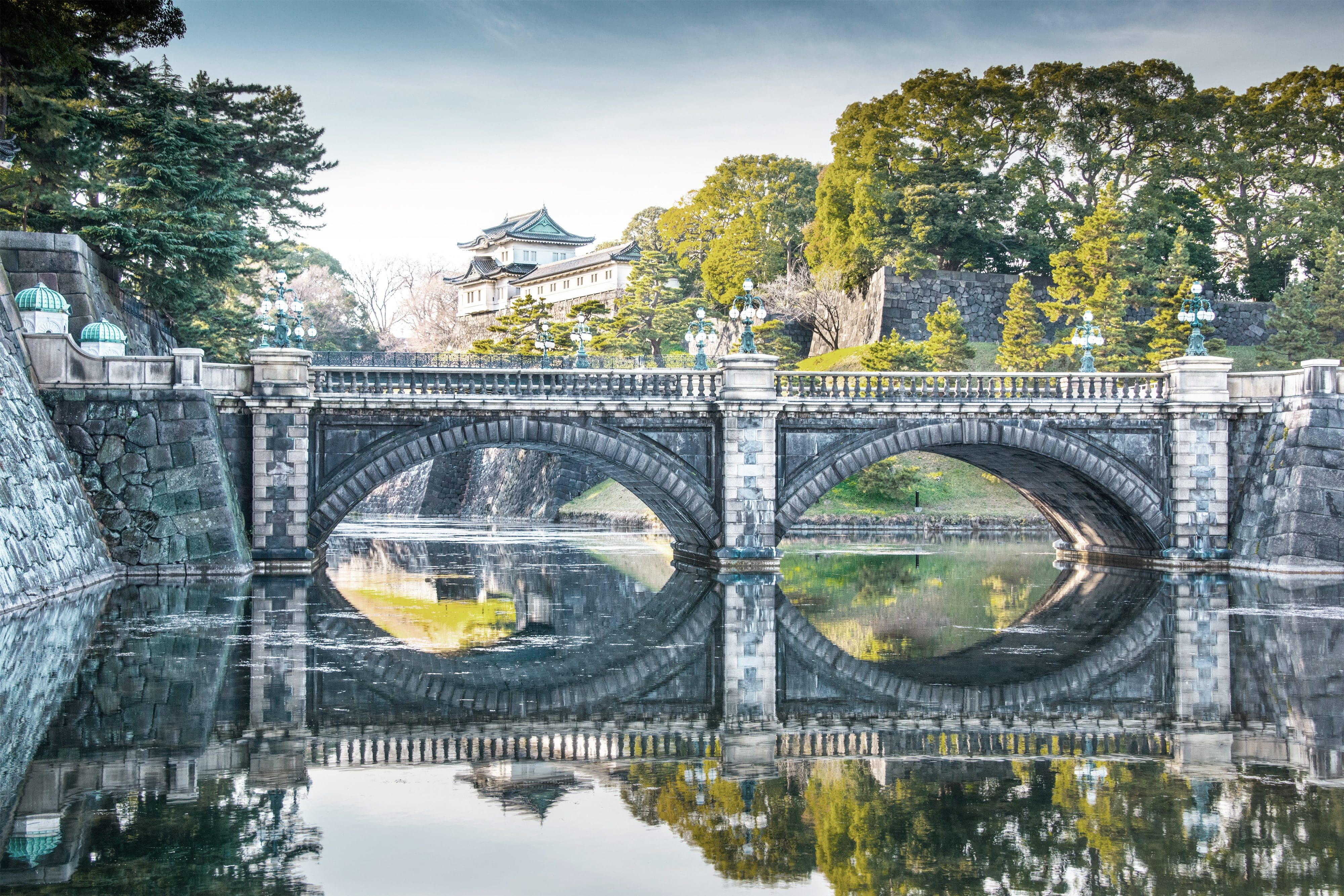 Bridge crossing the reflective water in Tokyo's Imperial Palace gardens