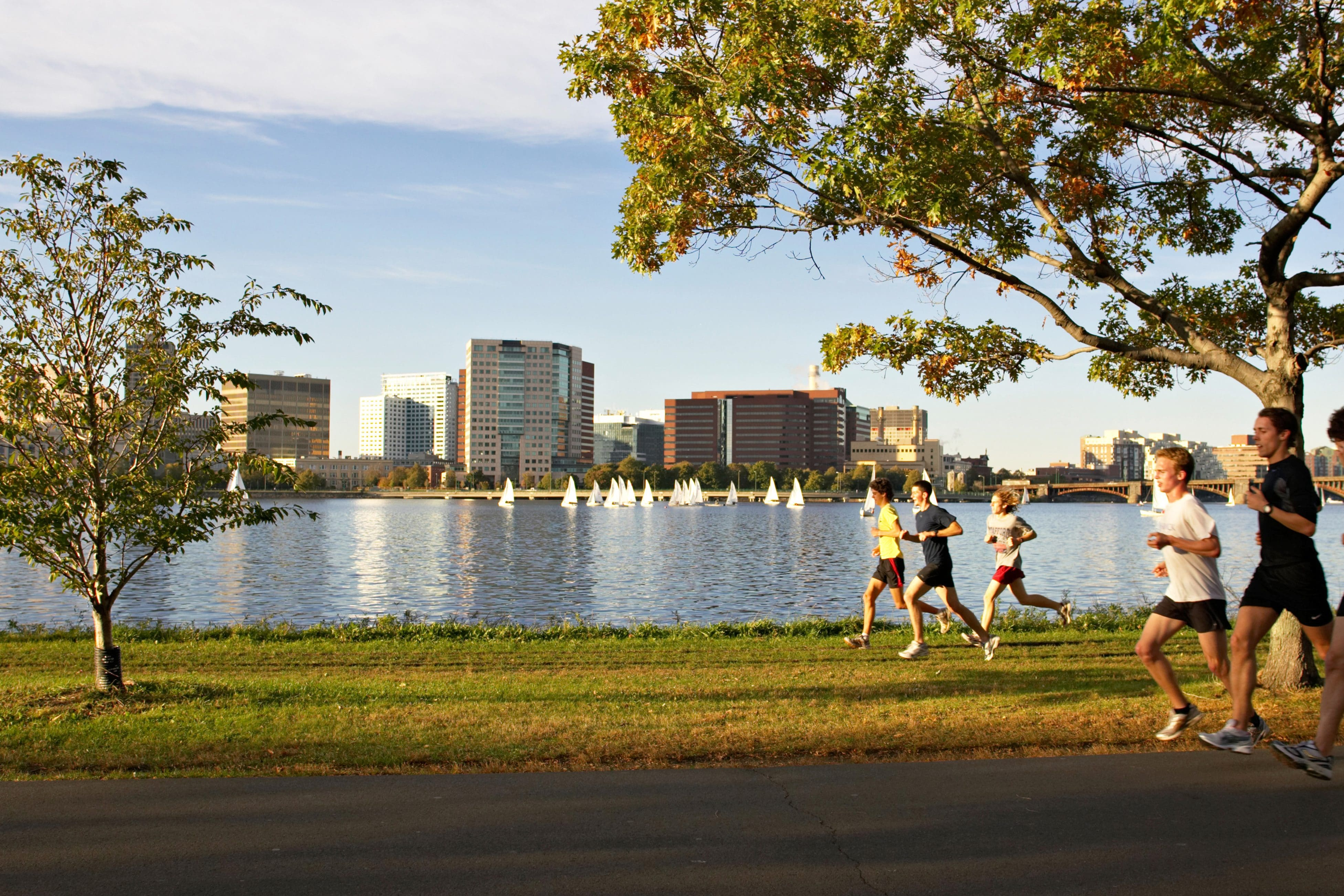 Runners make their way along Boston's Charles River bank in the early morning sun