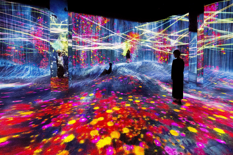 Visitors enjoy multi-coloured light installations at TeamLab