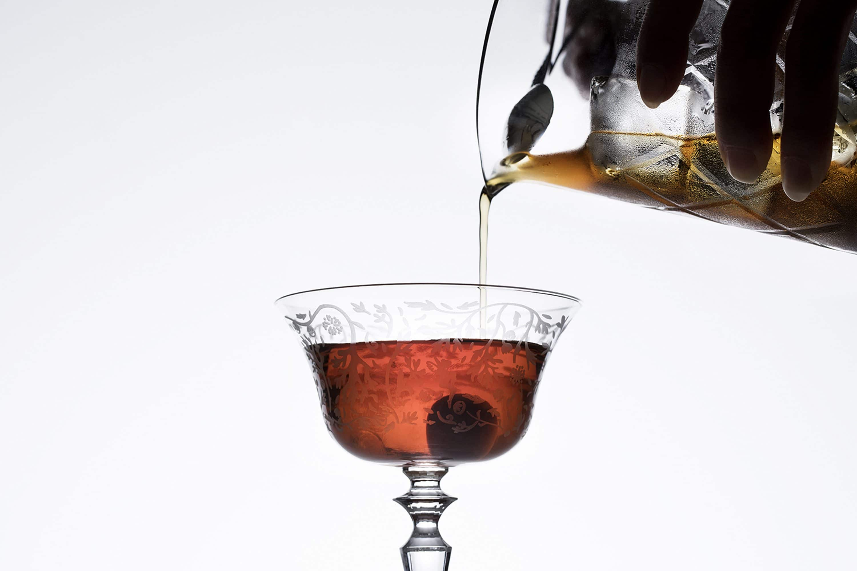 Manhattan cocktail being poured into a coupe glass