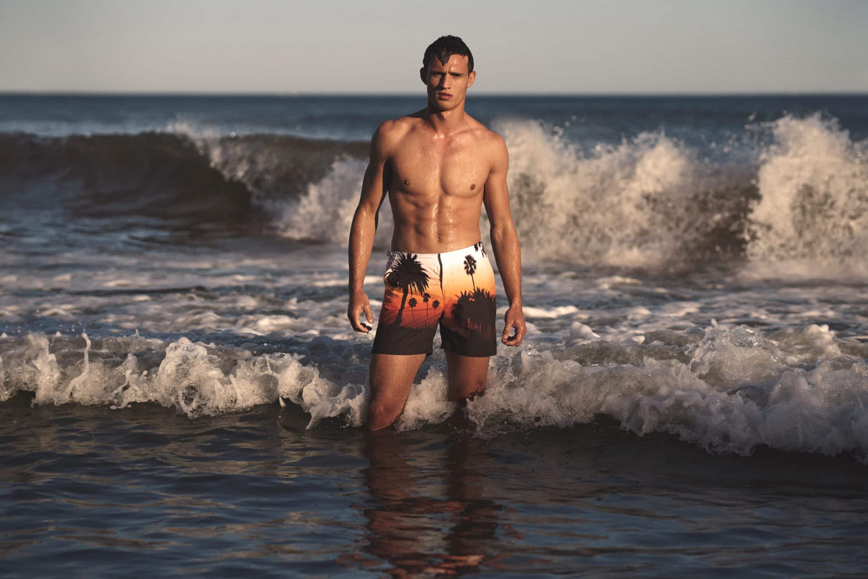Man poses in sea wearing Orlebar Brown swimshorts