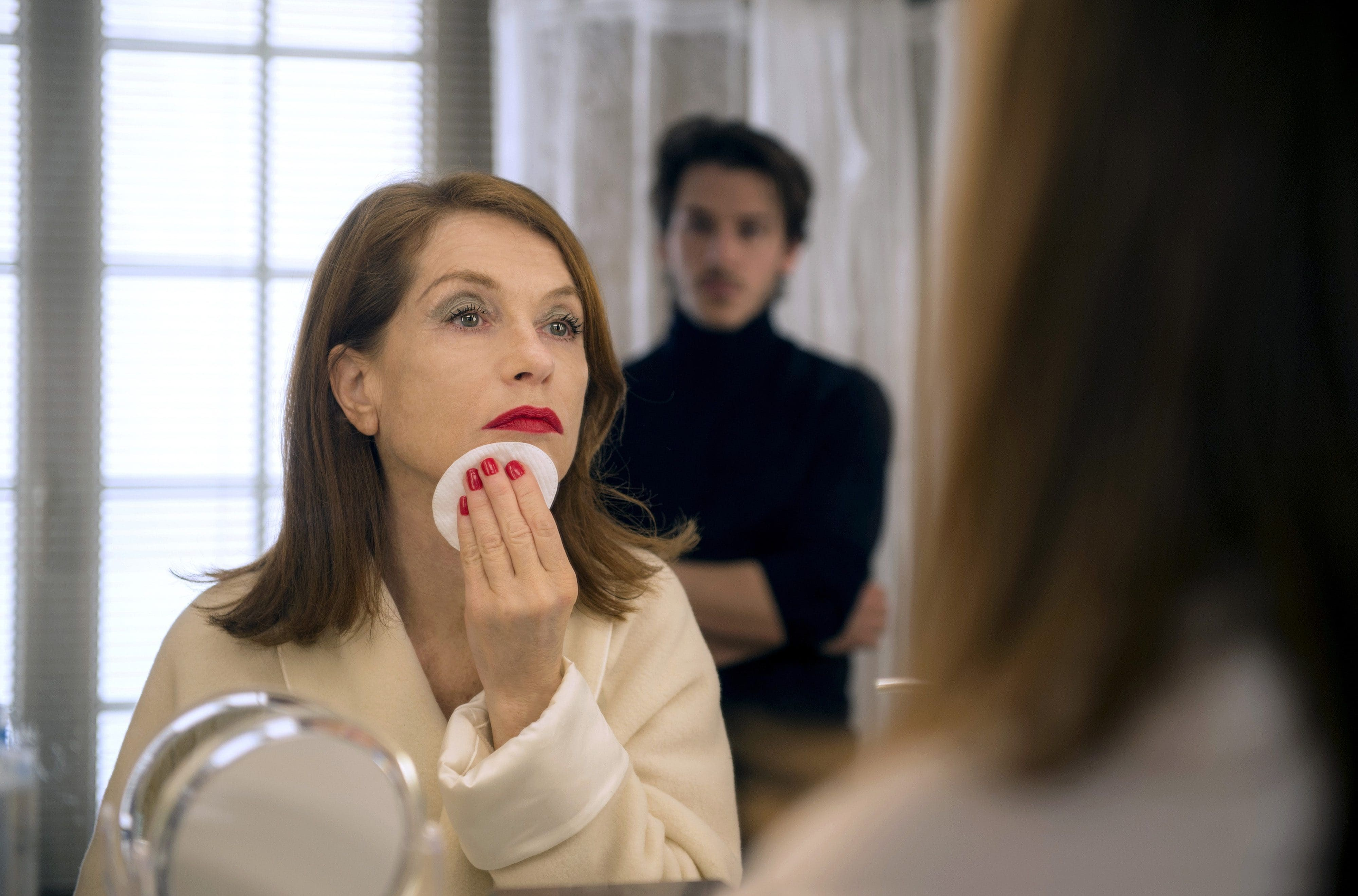 Isabelle staring into a bathroom mirror in a screenshot from her film Blanche Comme Neige