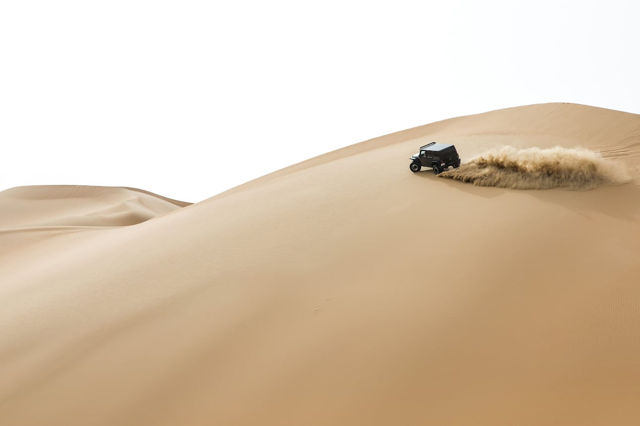 Car driving across the dunes in Abu Dhabi