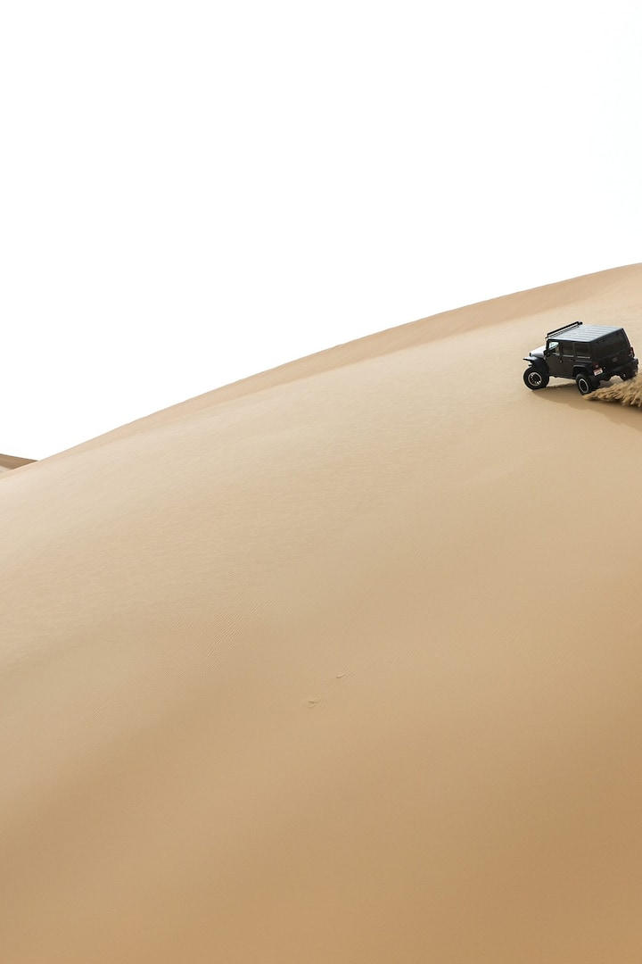 Off-road vehicle drives over undulating sand dunes, Dubai